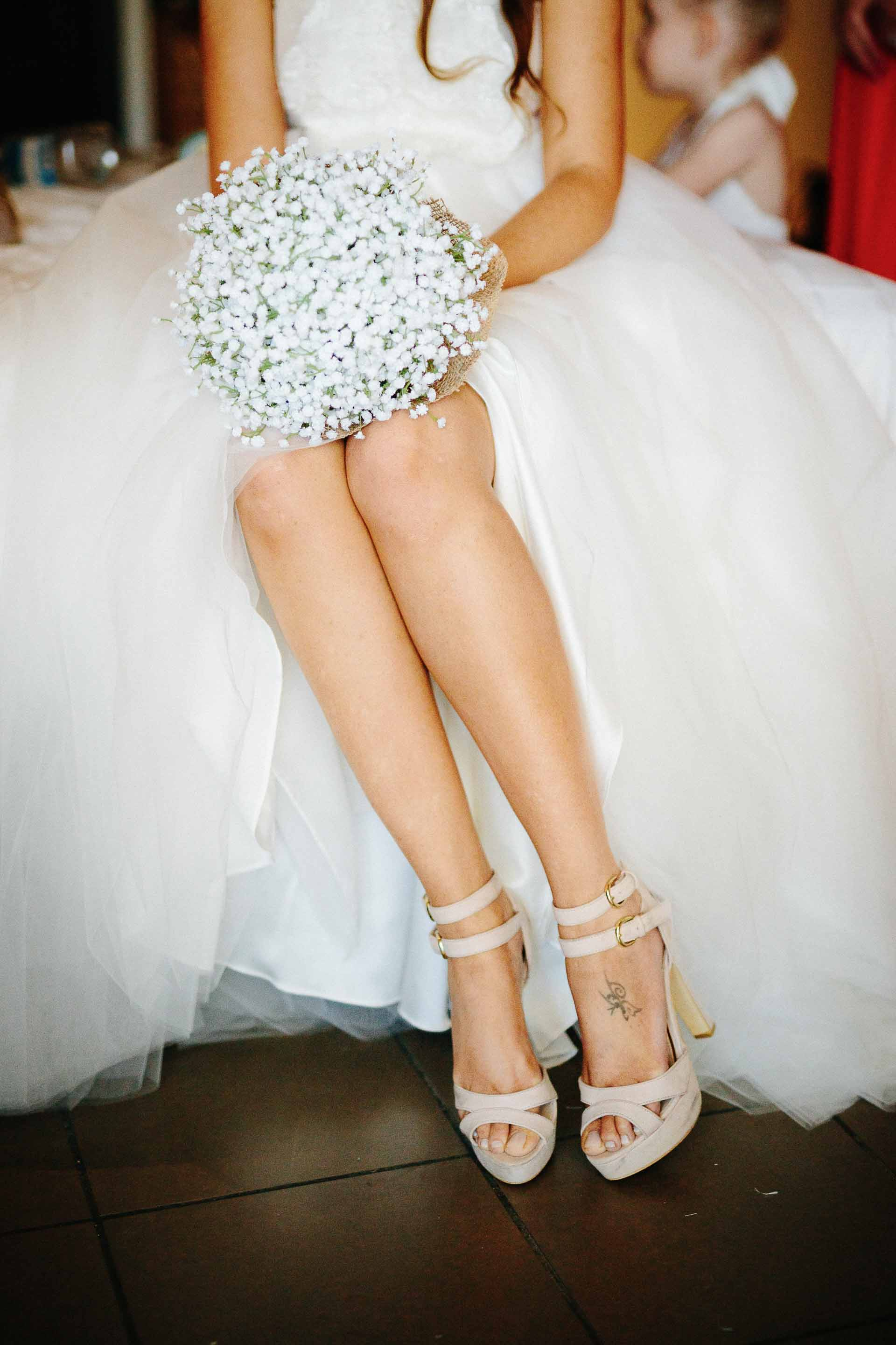 brides legs with her shoes and bouquet
