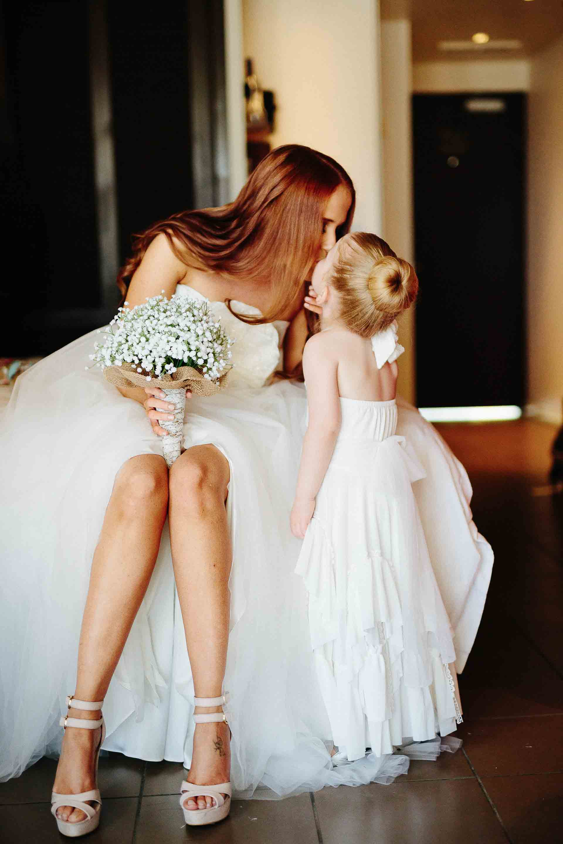 the bride receiving a kiss from the flower girl