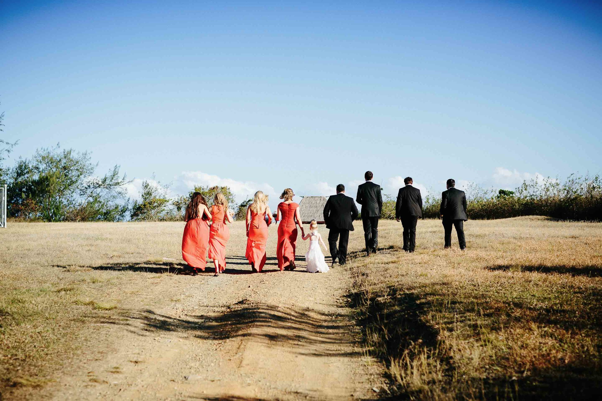 the bridal party walking off along a dusty dirt road