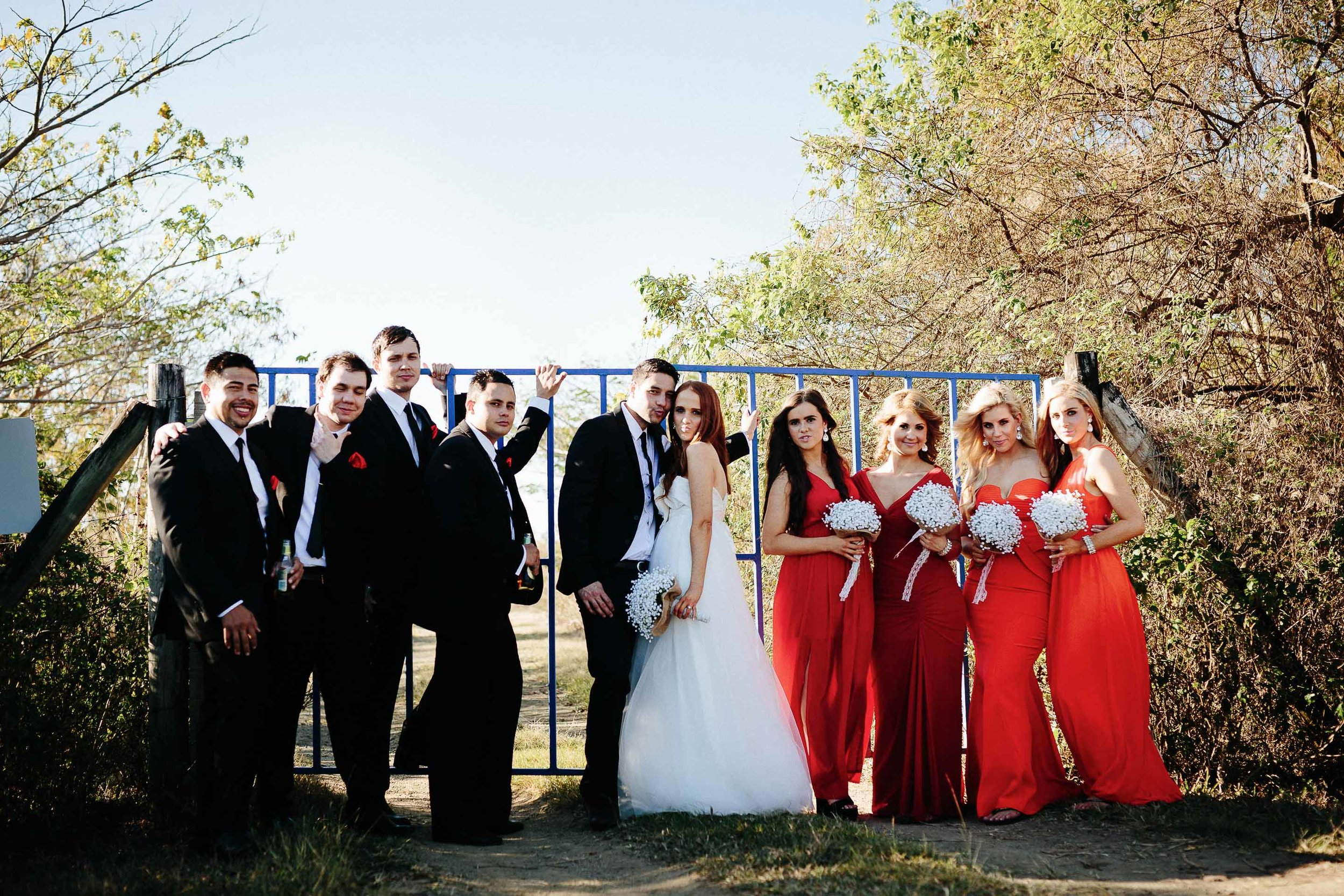 the bridal party sharing a light moment next to a blue gate