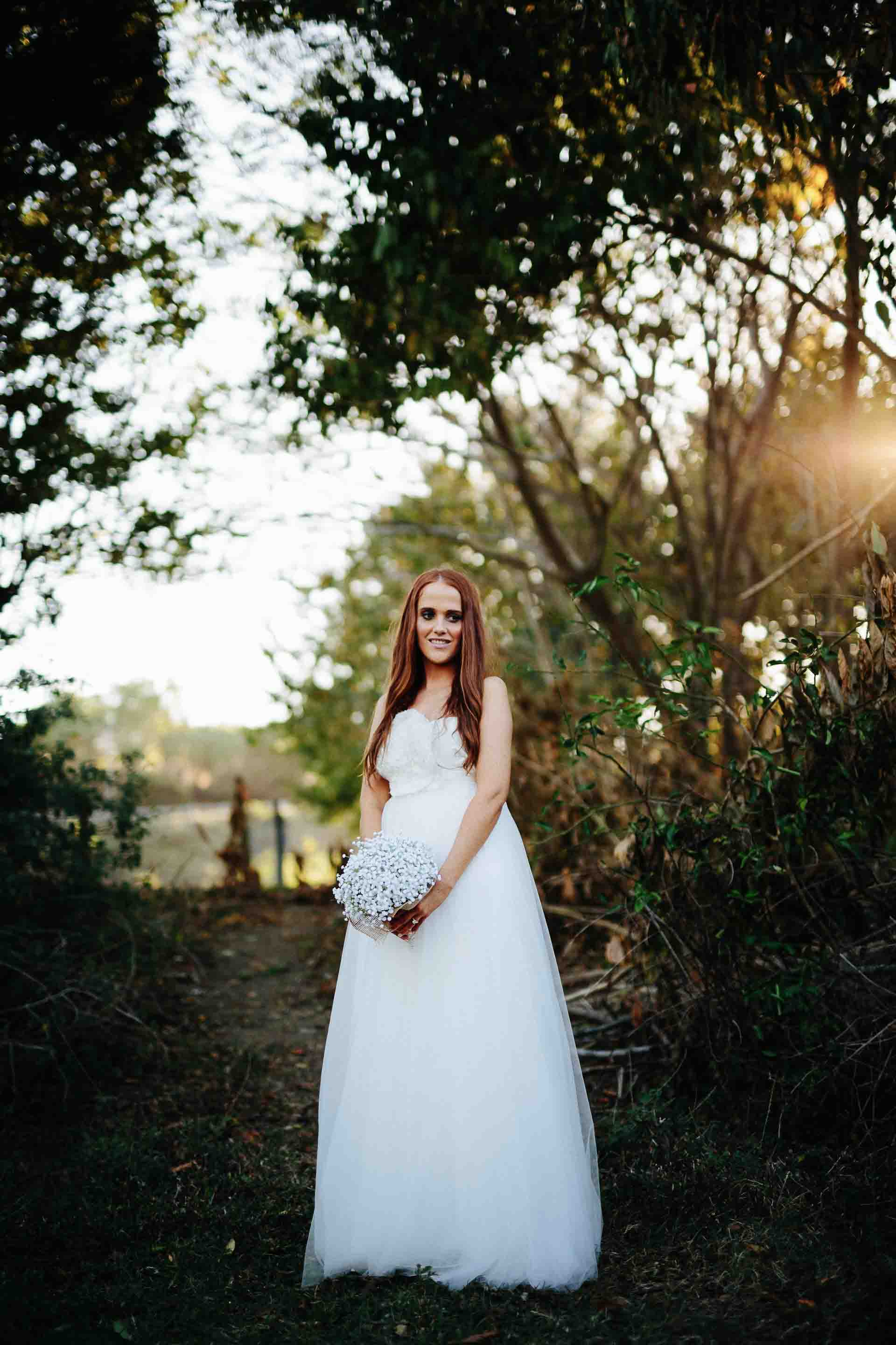 bride standing alone with sun behind trees in the background