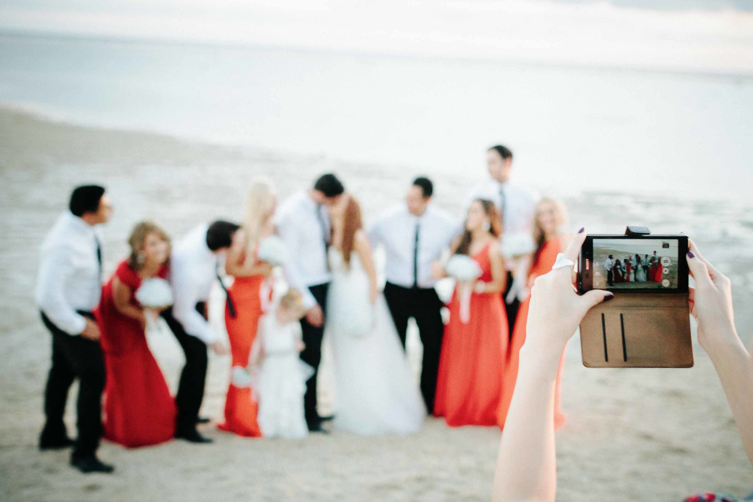 a guest taking a picture of the bridal party on the beach at sunset with their camera phone