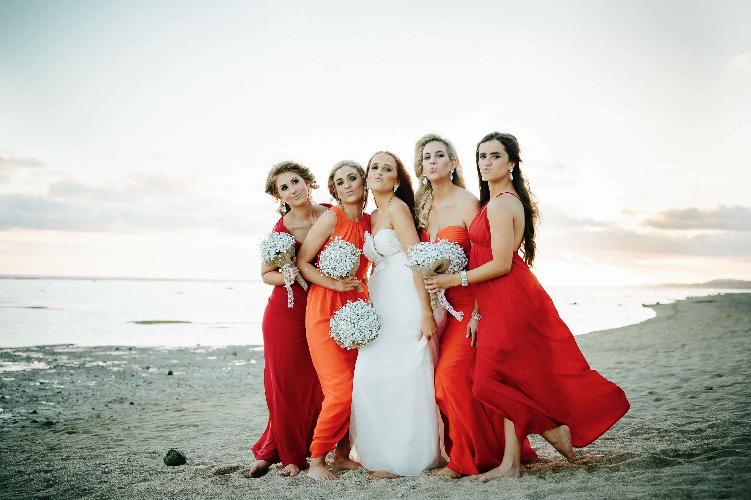bride and bridesmaids pulling a funny face on the beach at sunset