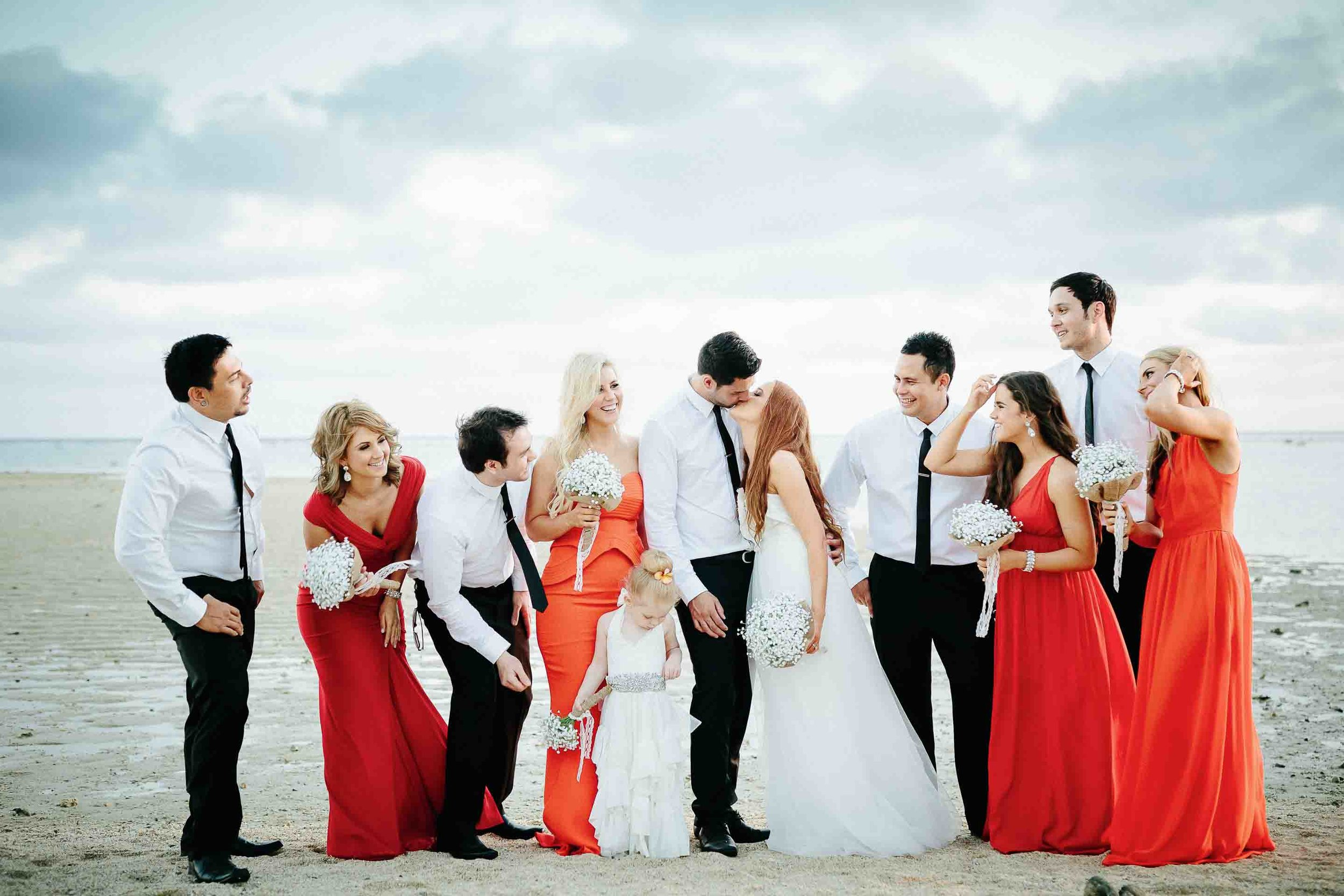 husband and wife kissing as the rest of the bridal party looks on