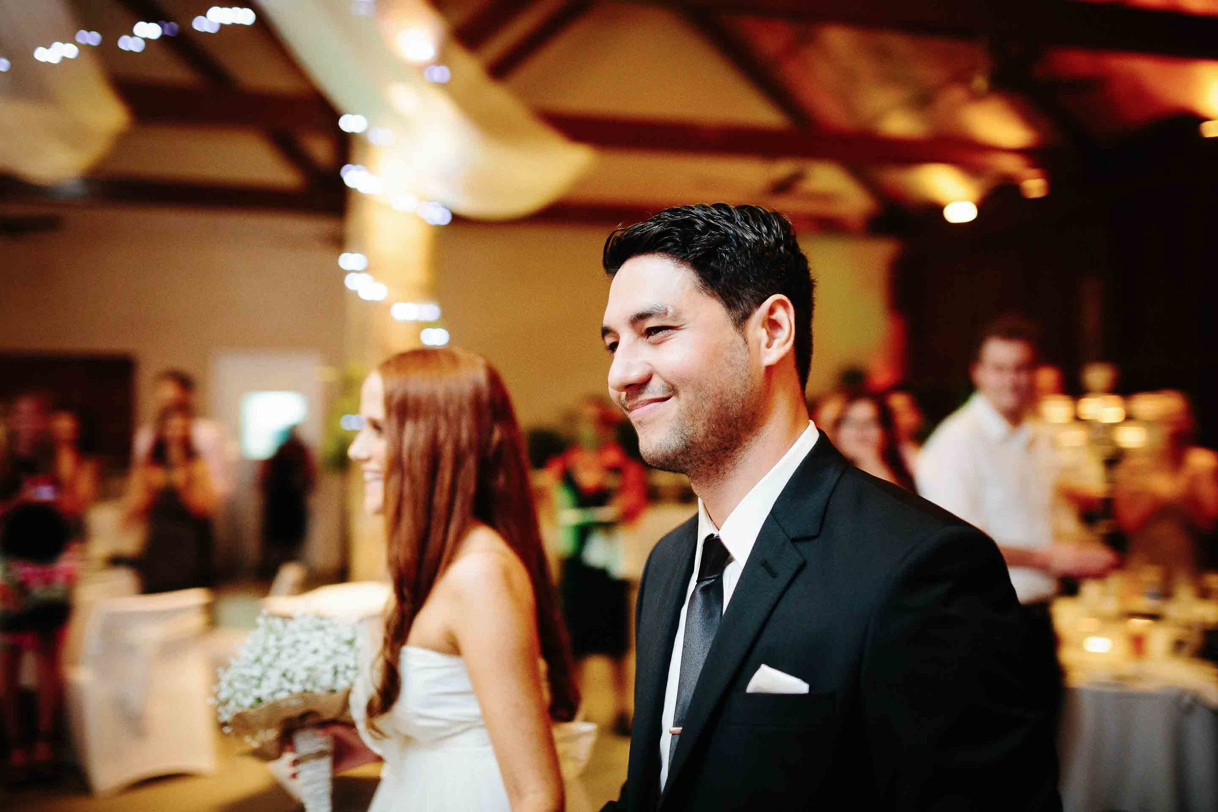 groom smiling as he leads his bride to their dinner table