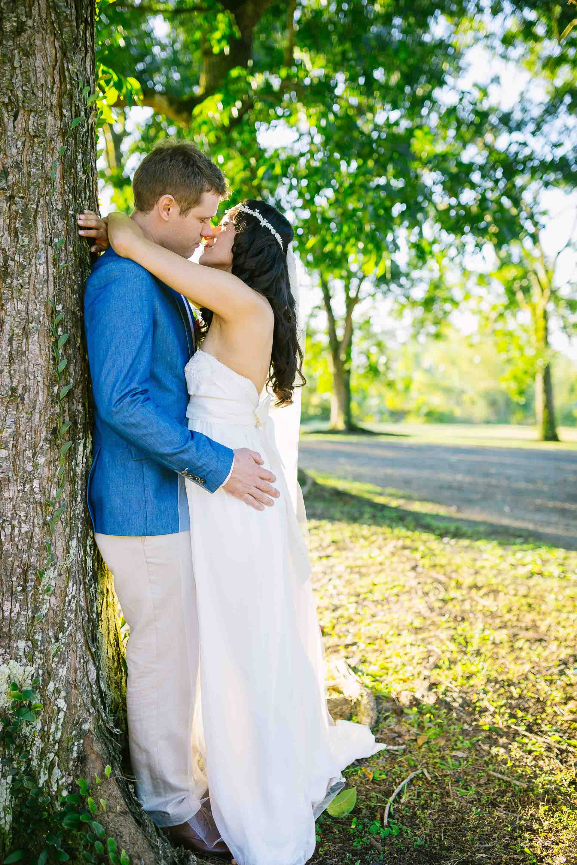 the couple kiss while leaning against a large tree