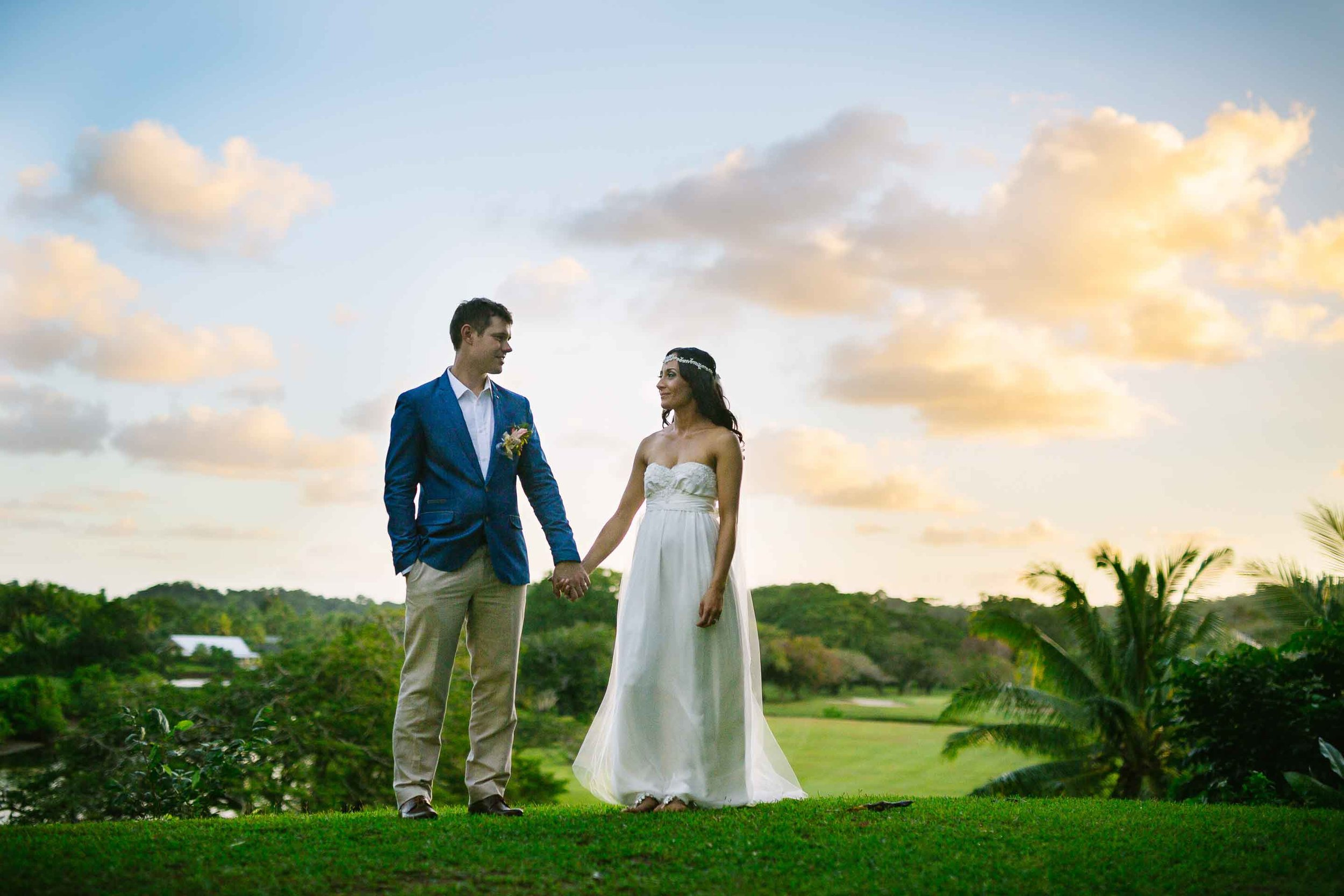 the newlyweds holding hands with golden clouds behind them
