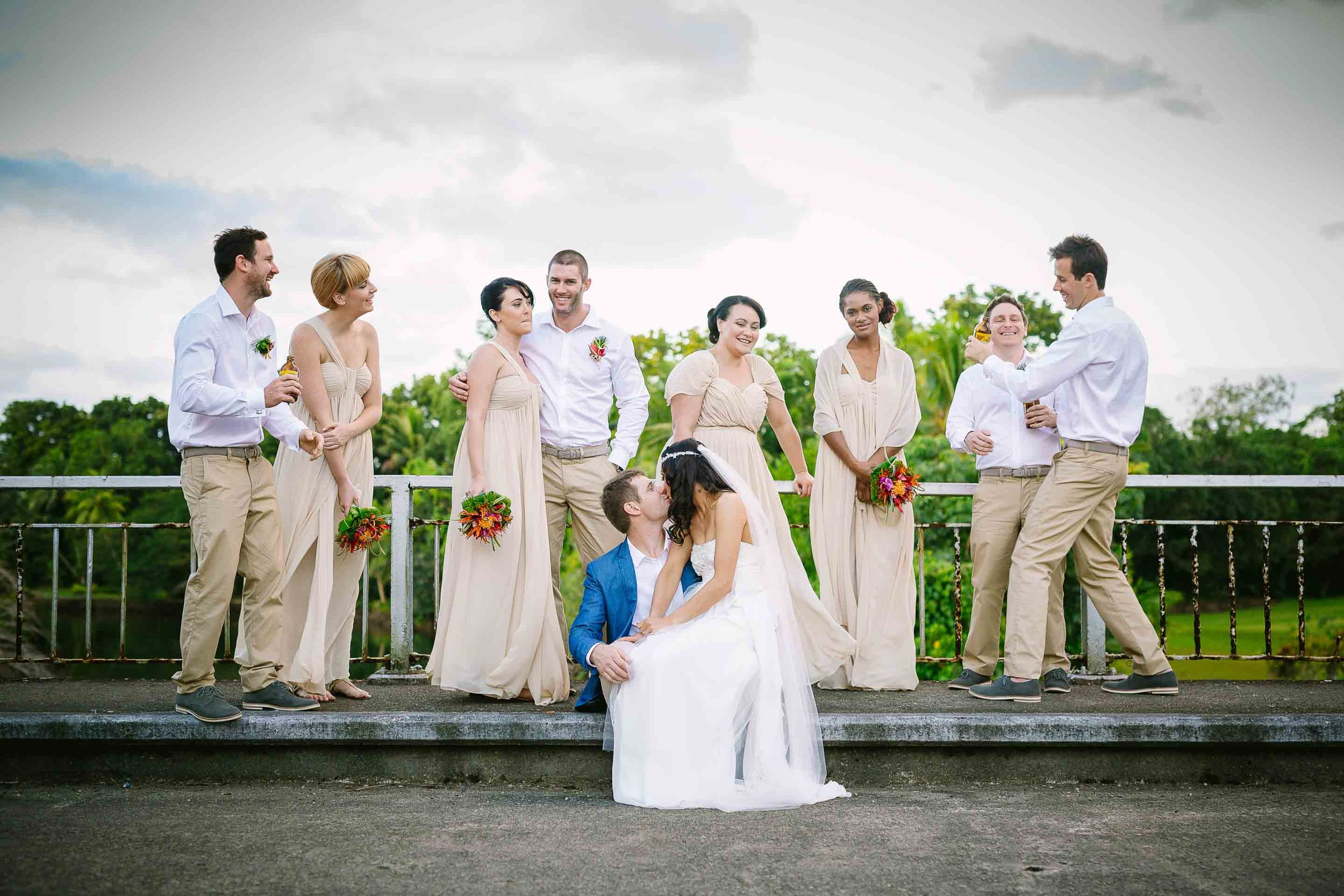the bridal party sharing a fun moment on an old bridge