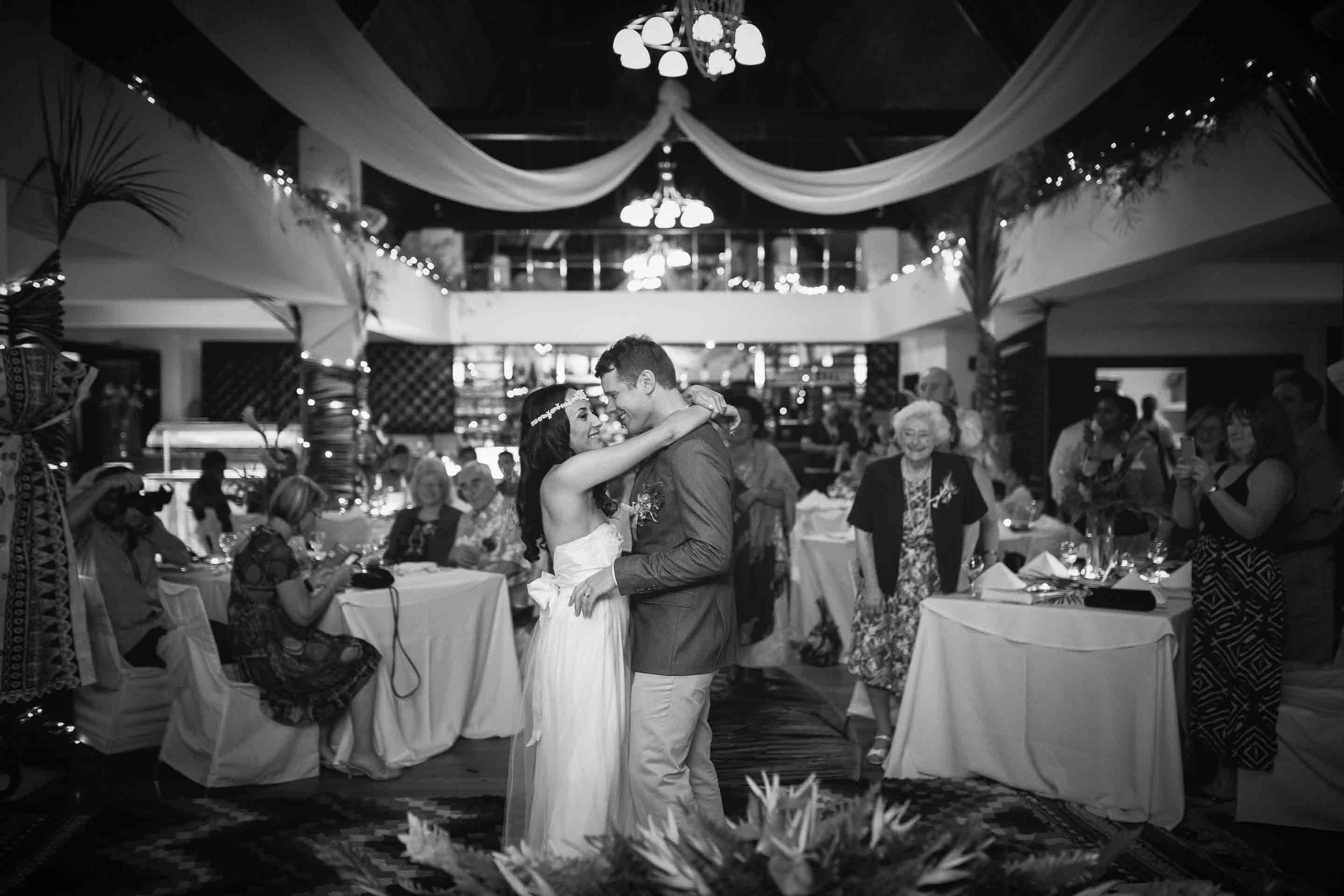 black and white of the first dance as husband and wife as guests look on
