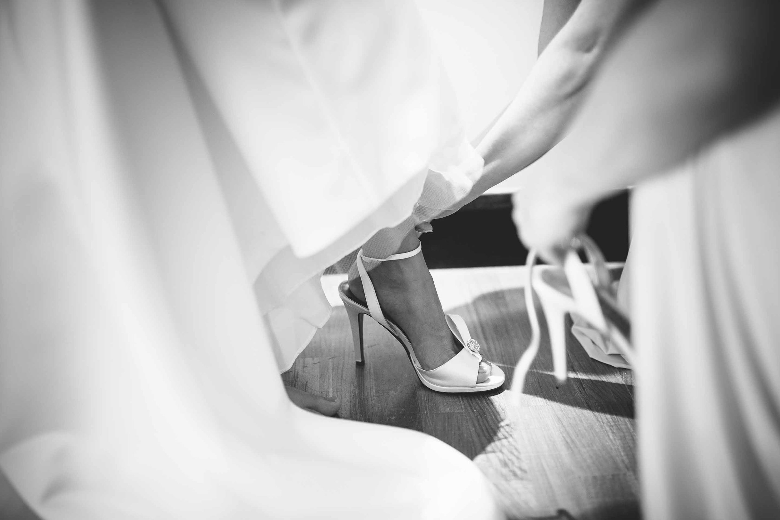 the brides shoes being done up