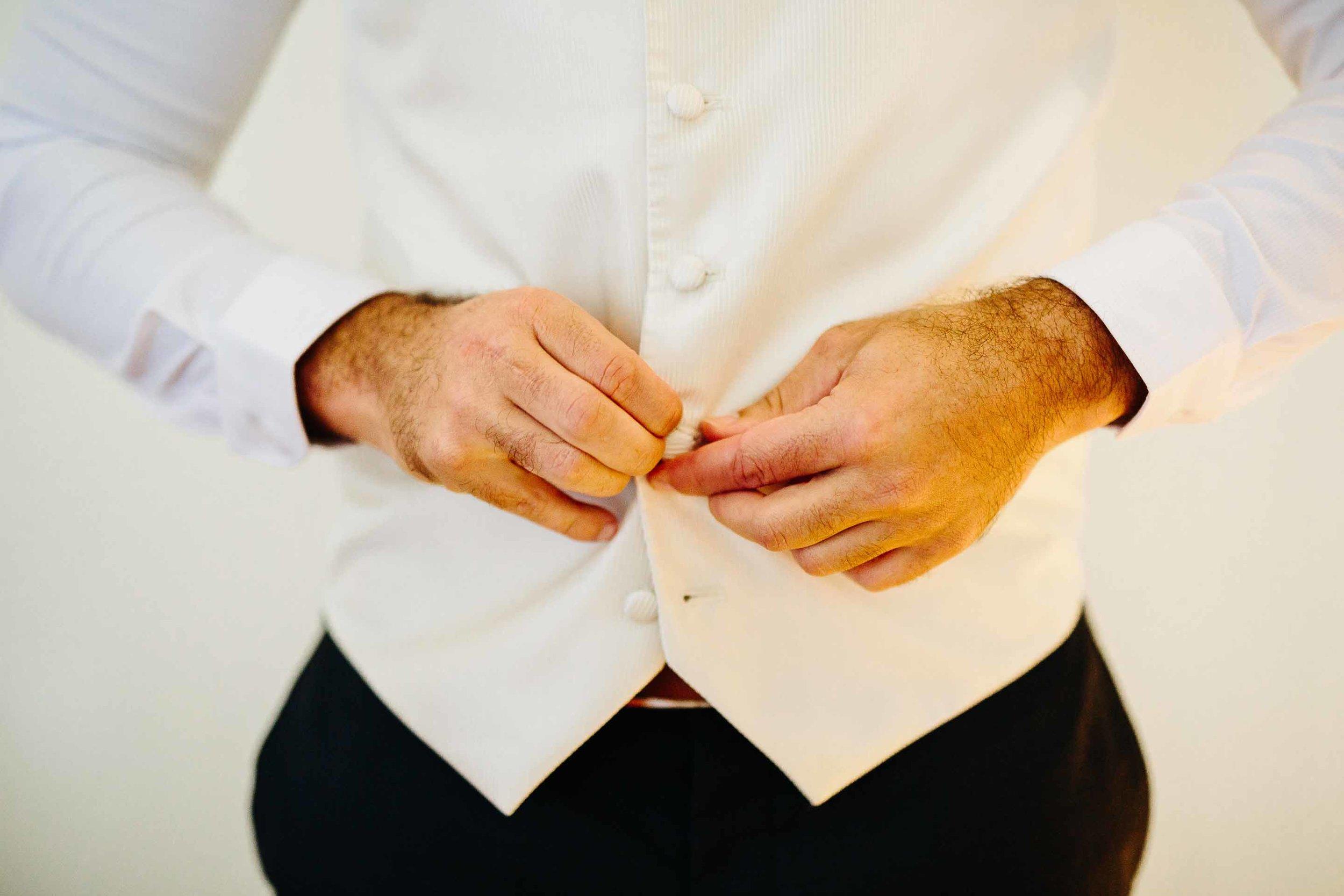 groom doing up his waist coat