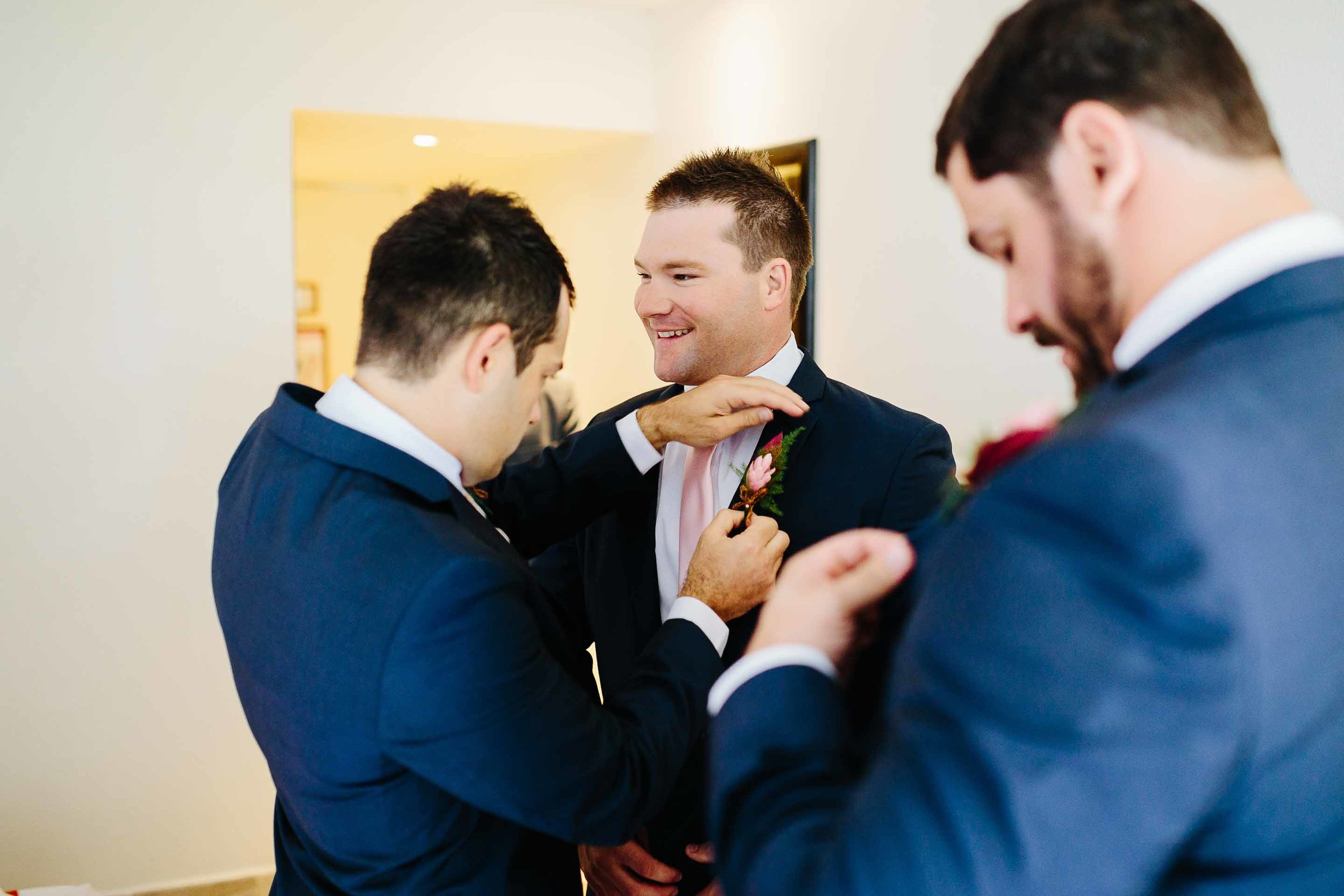 groom helping groomsman with boutonniere