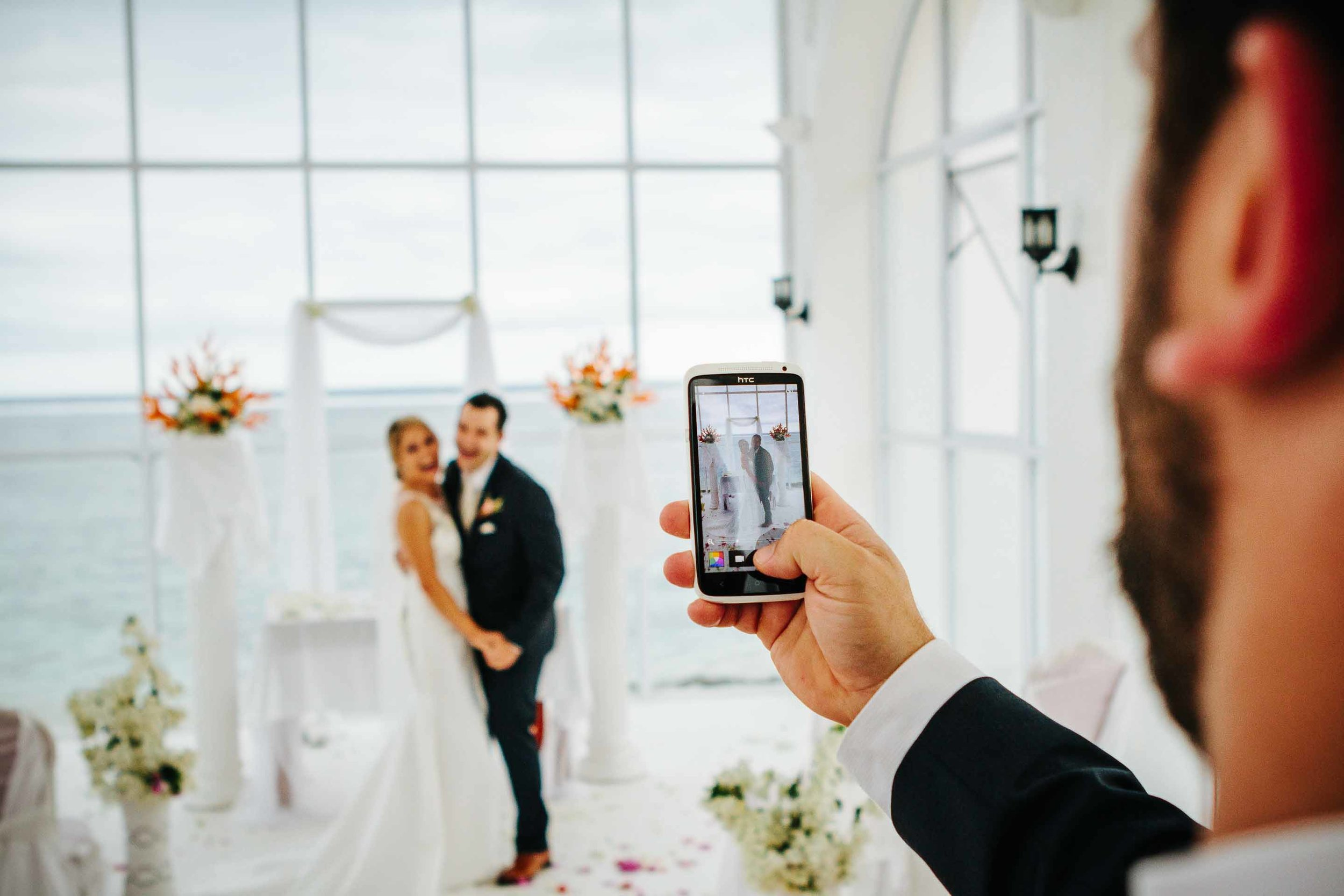 best man grabbing a picture of the couple