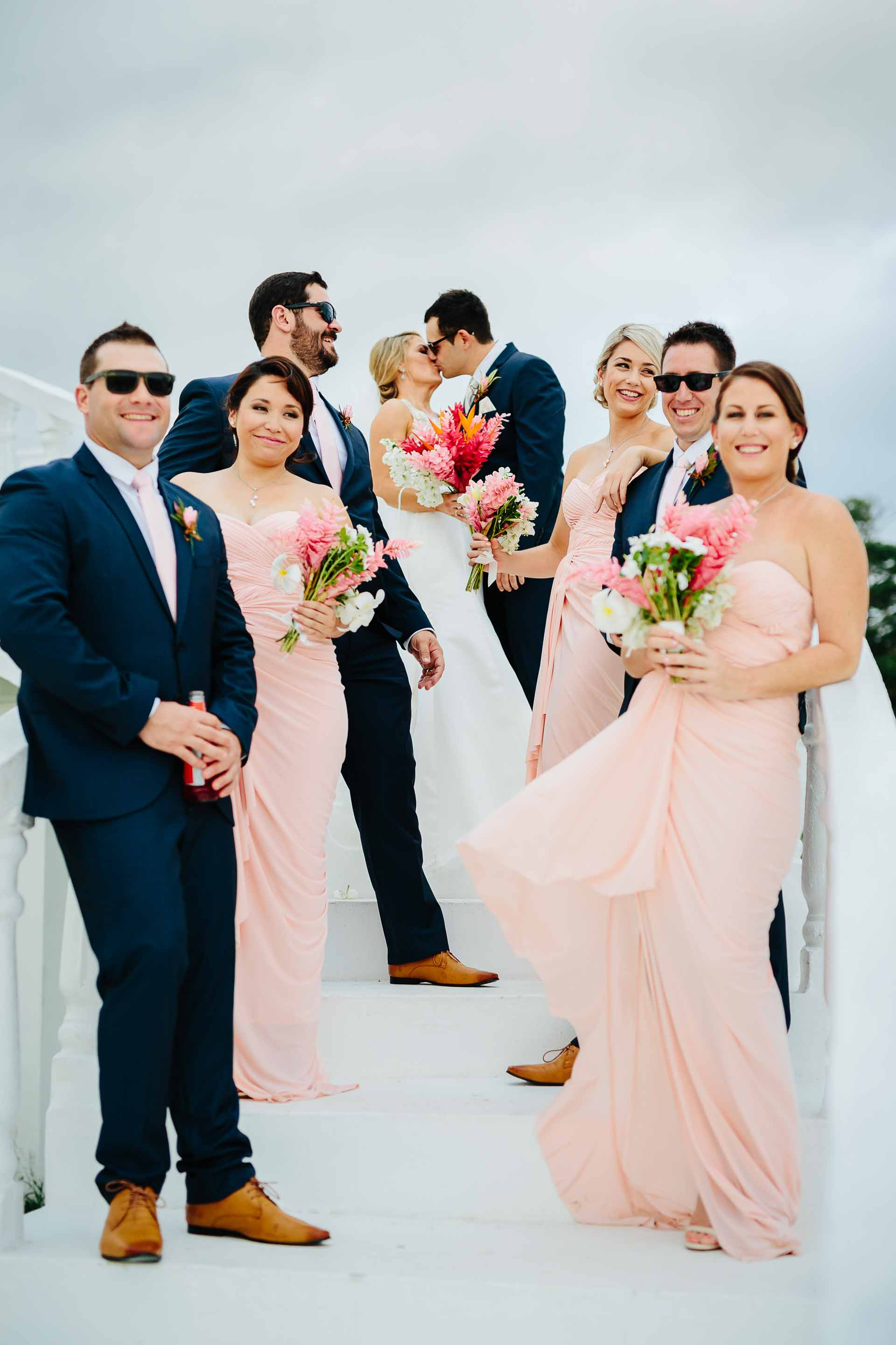 bridal party on stairs with couple kissing