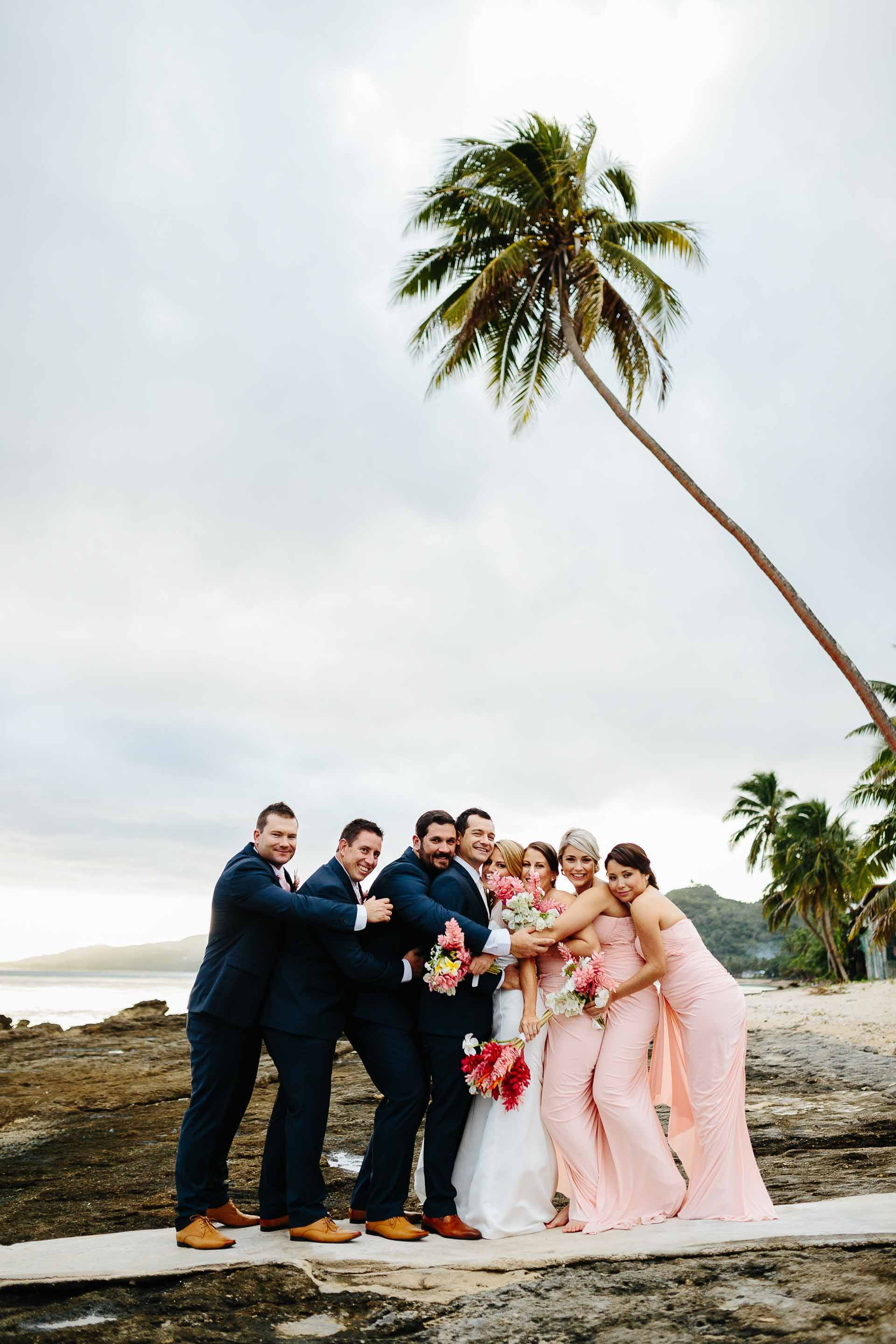 bridal party hugging on the beach