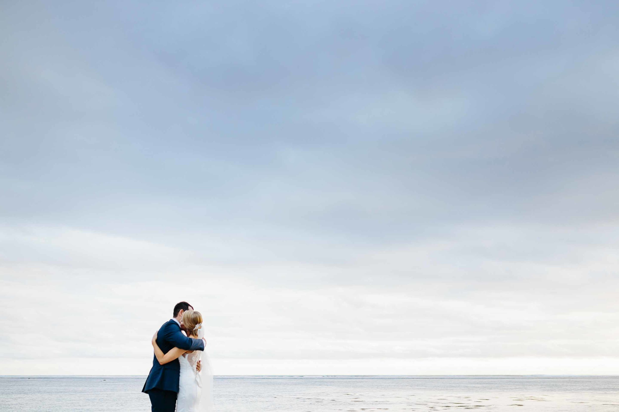 couple hugging with cloudy sky behind them