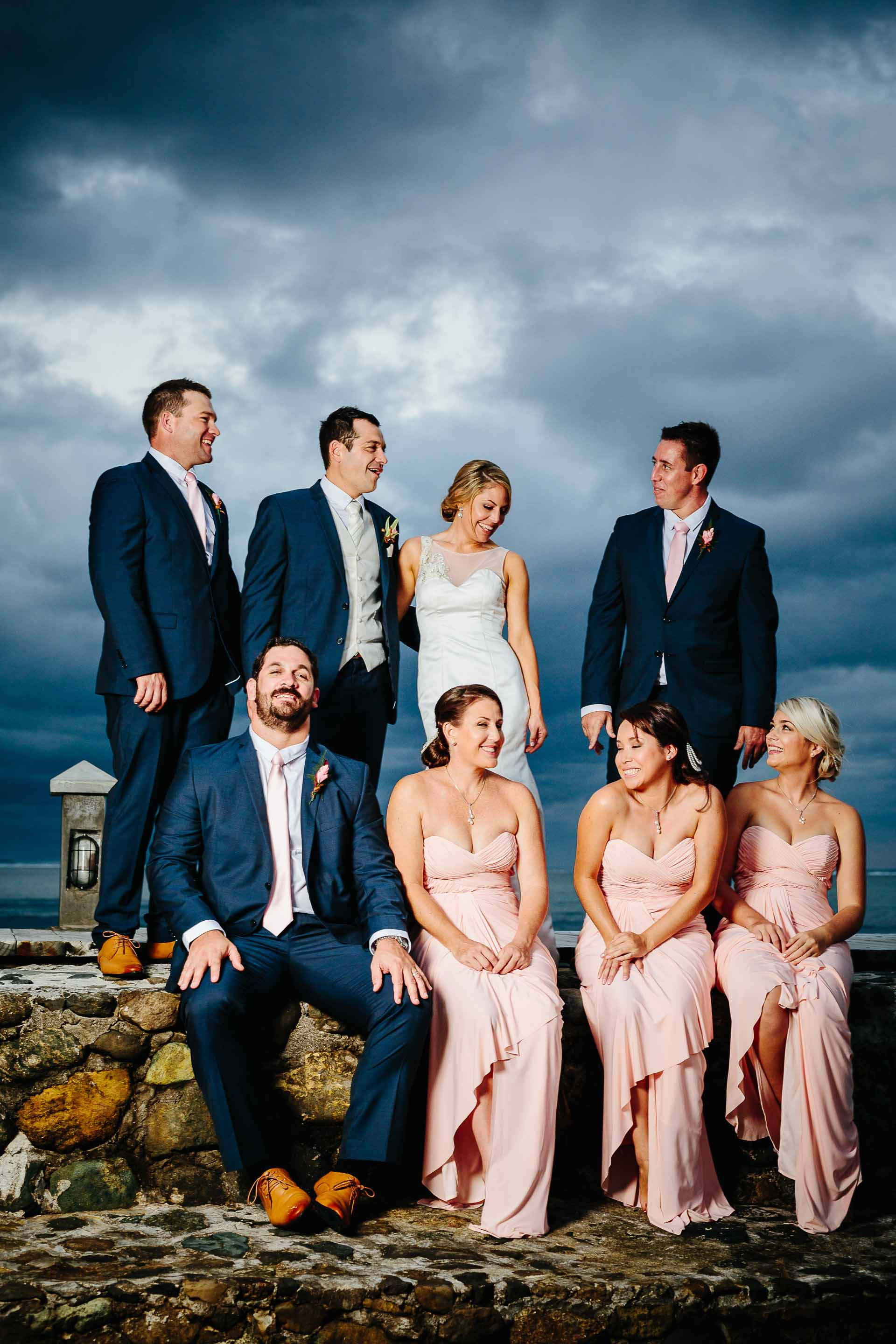 bridal party sitting on a pier with dramatic dark clouds behind them