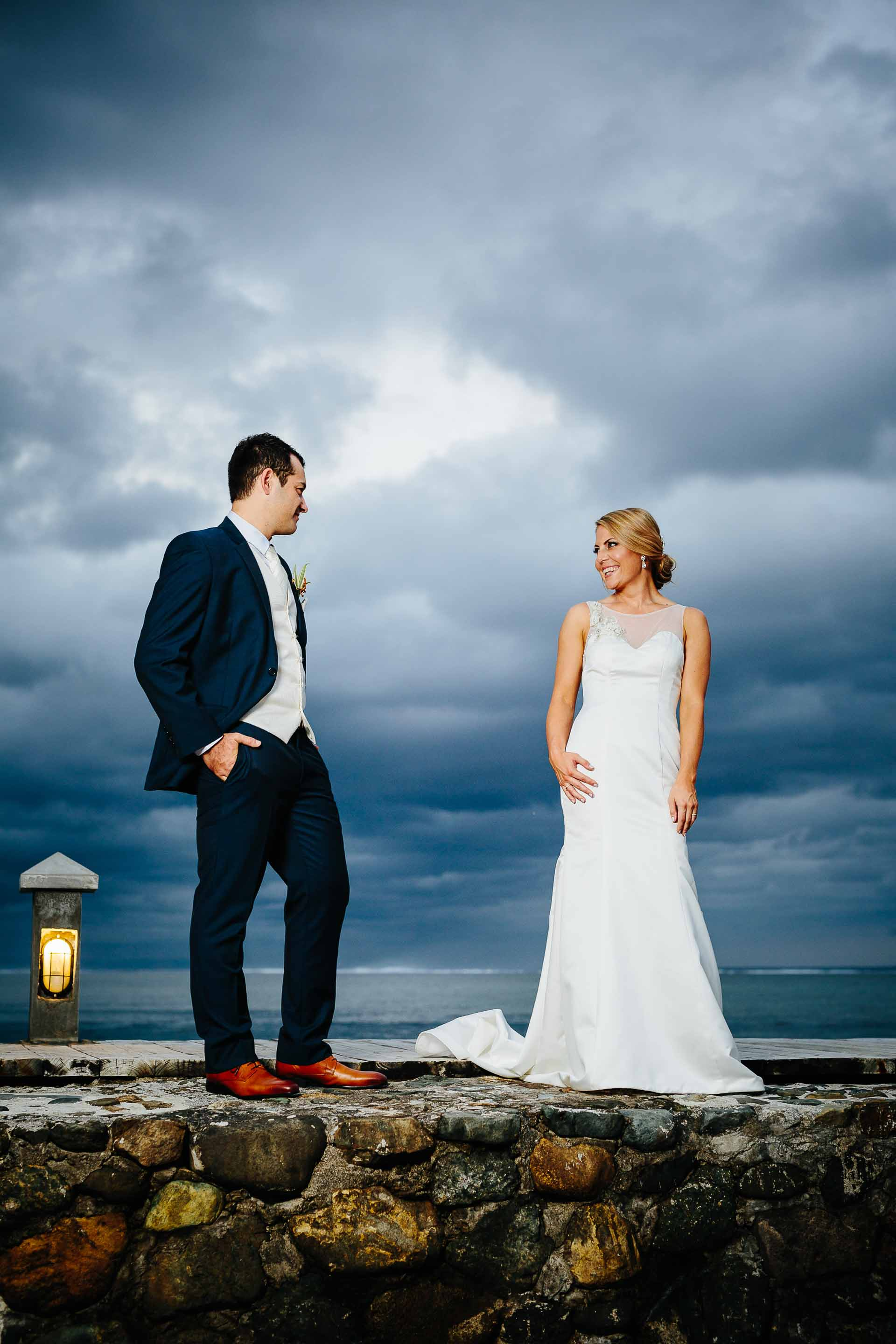 couple on pier with dramatic clouds behind them