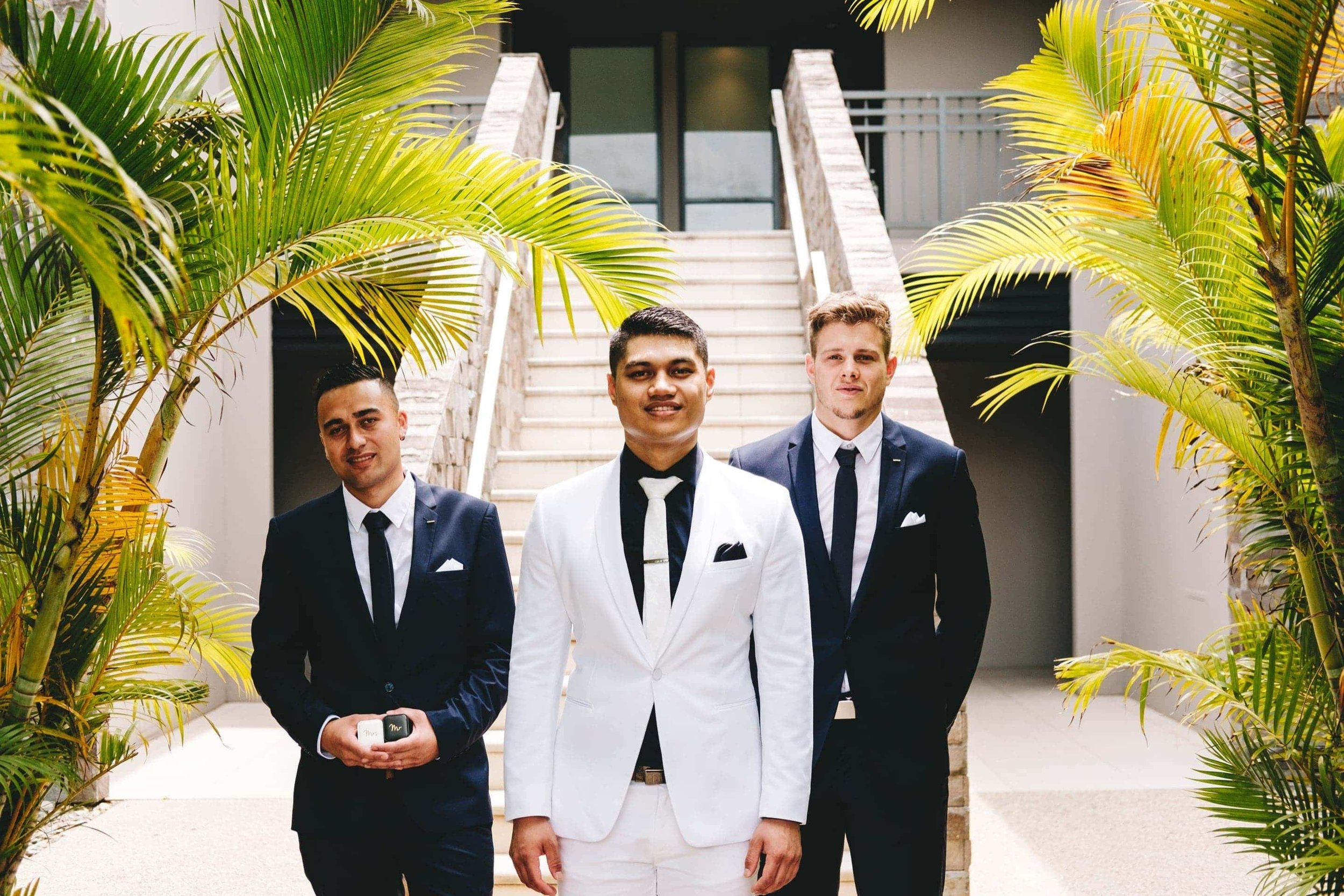 the groom and groomsmen posing for a photo after getting ready