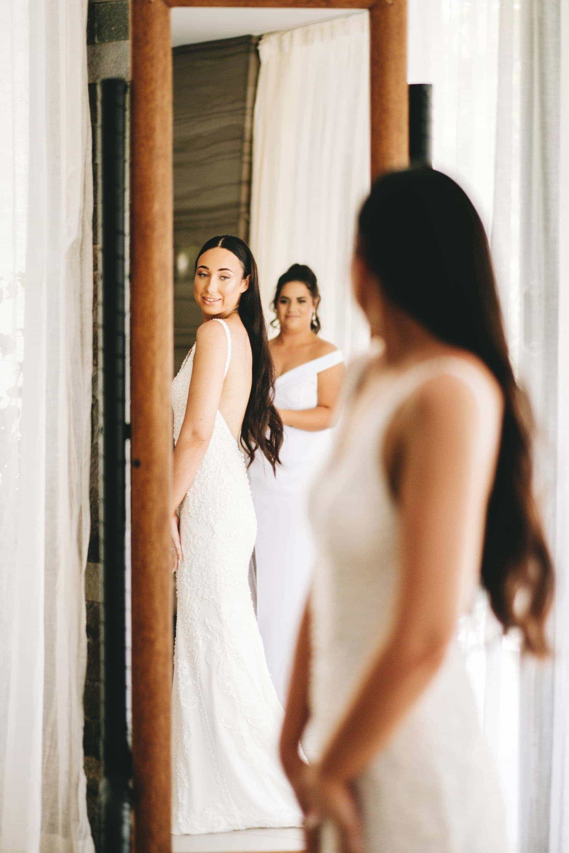 the bride looking at herself in the mirror as her bridesmaid looks on