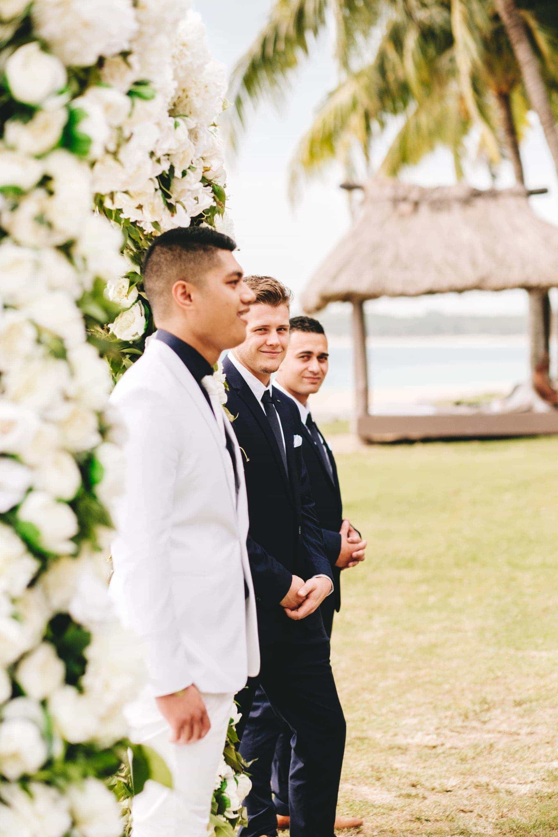 the groom waiting excitedly at ceremony arch as the groomsman and best man watch on