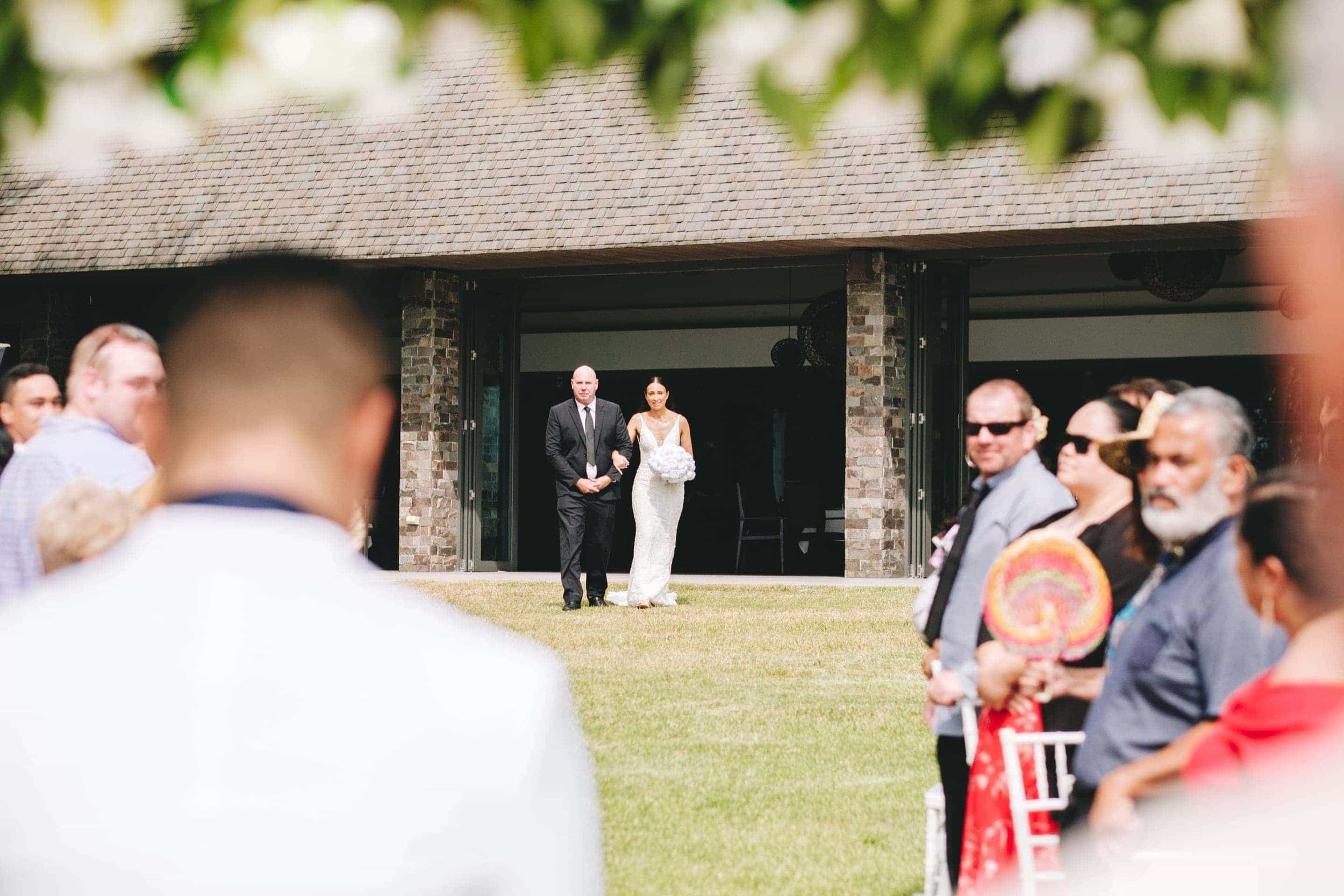the bride and her father walking down the lawn aisle in front of the Navo Restaurant.