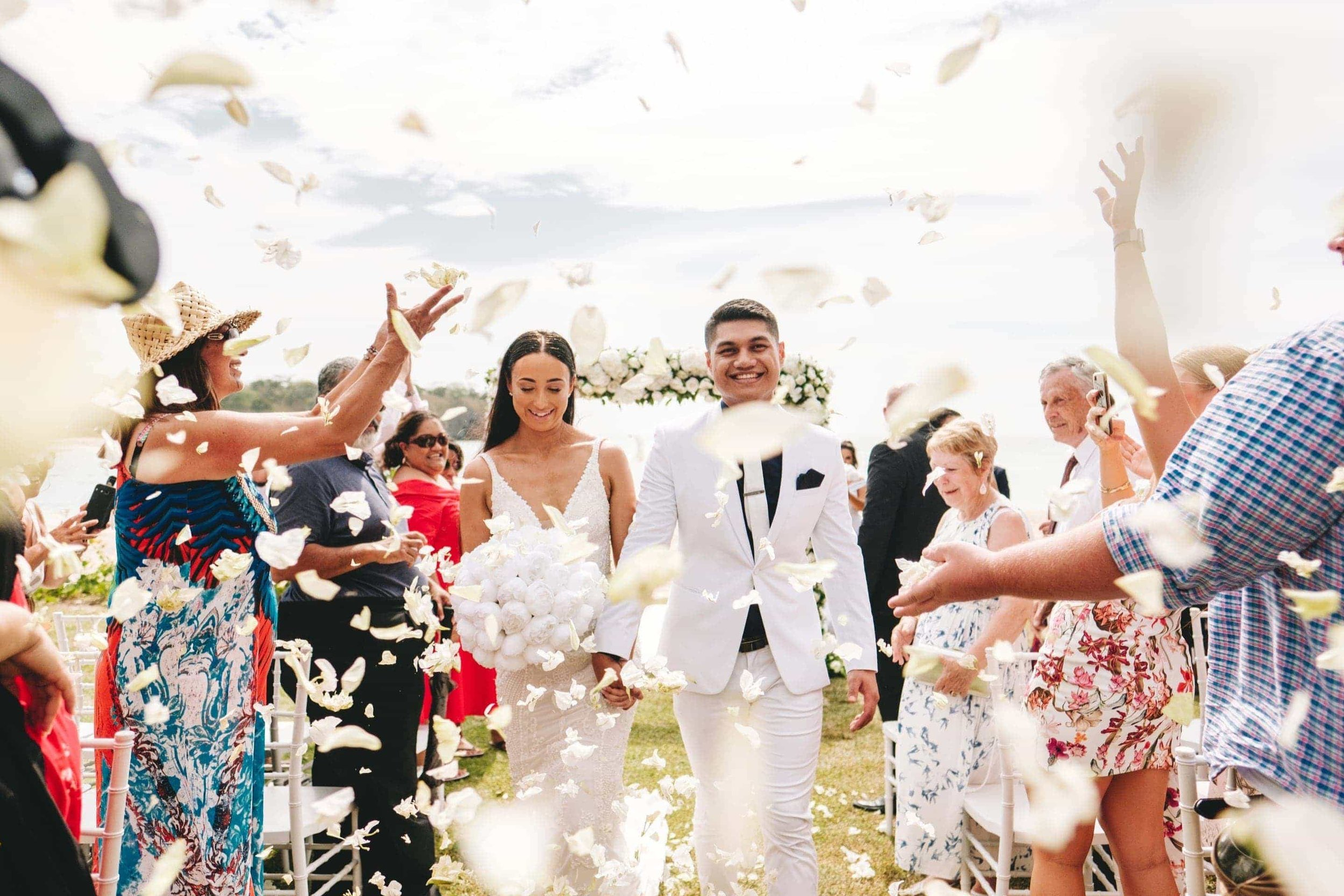 the couple showered in tropical flower confetti as the walk down the aisle together after the wedding ceremony