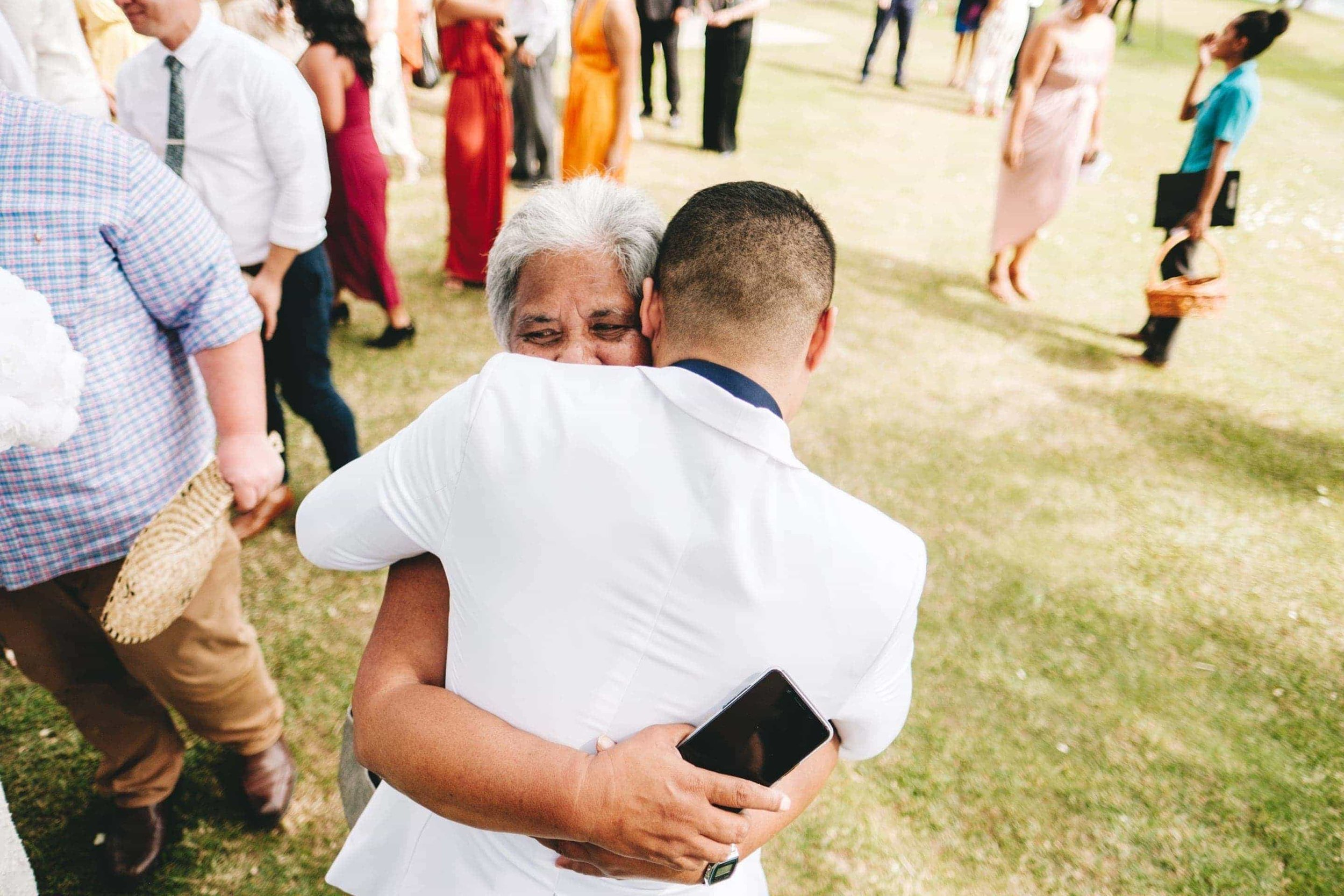 the groom embracing his grandmother after the ceremony
