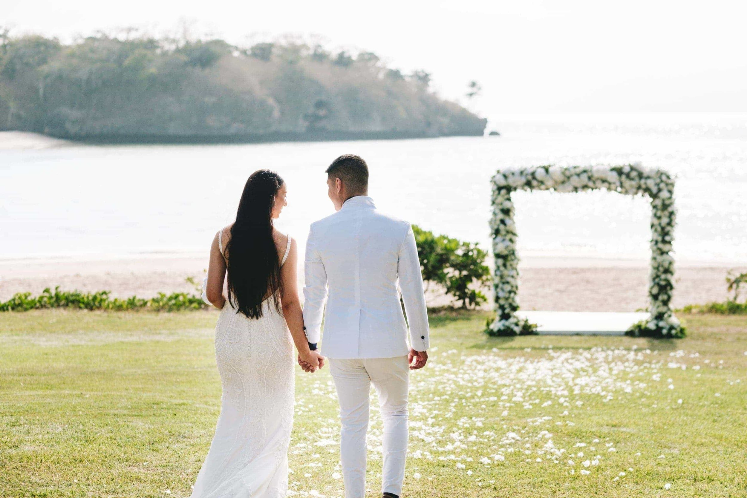 the bride and groom walking down the aisle together with Natadaloa beach and Navo Island in the background