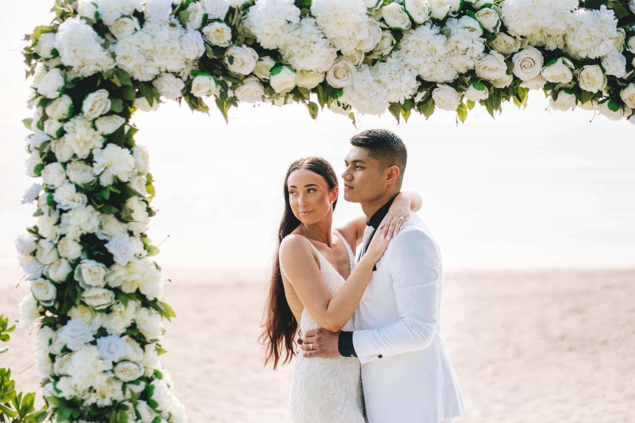 The newlyweds embrace under their white tropical wedding arch
