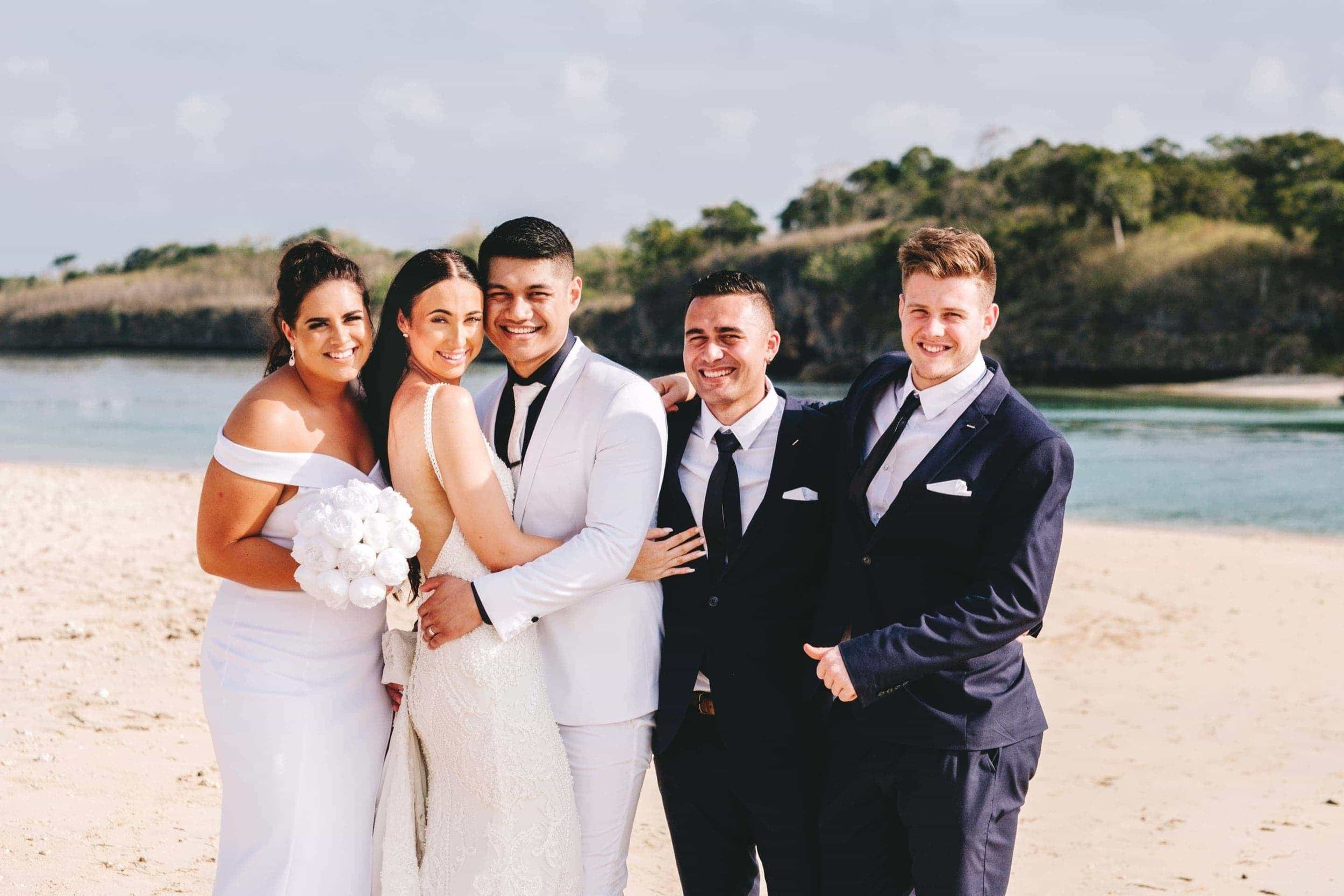 the bridal party embrace as they pose for a photo on Natadola beach with Navo Island in the background