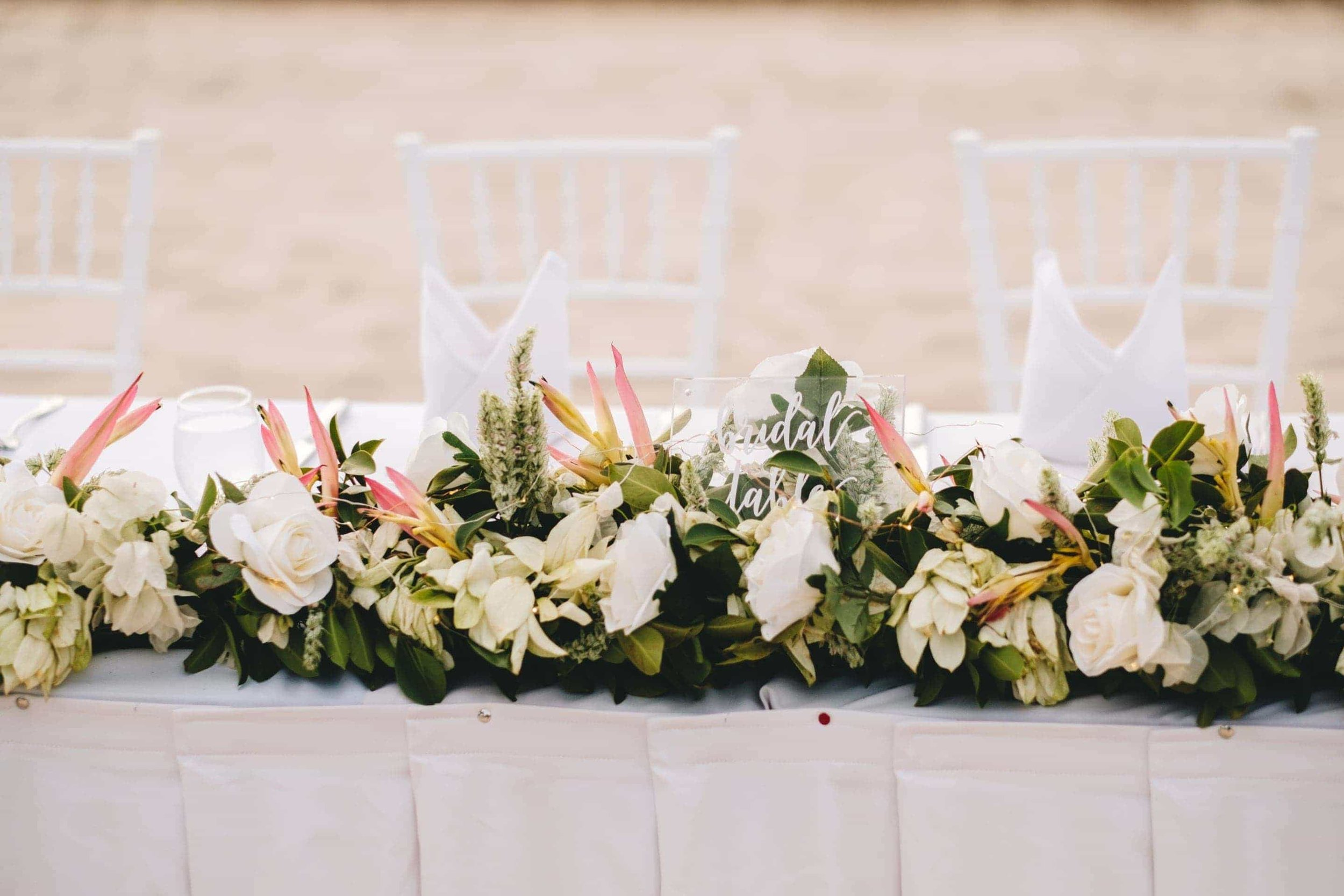 the bridal table covered in white tropical flowers.