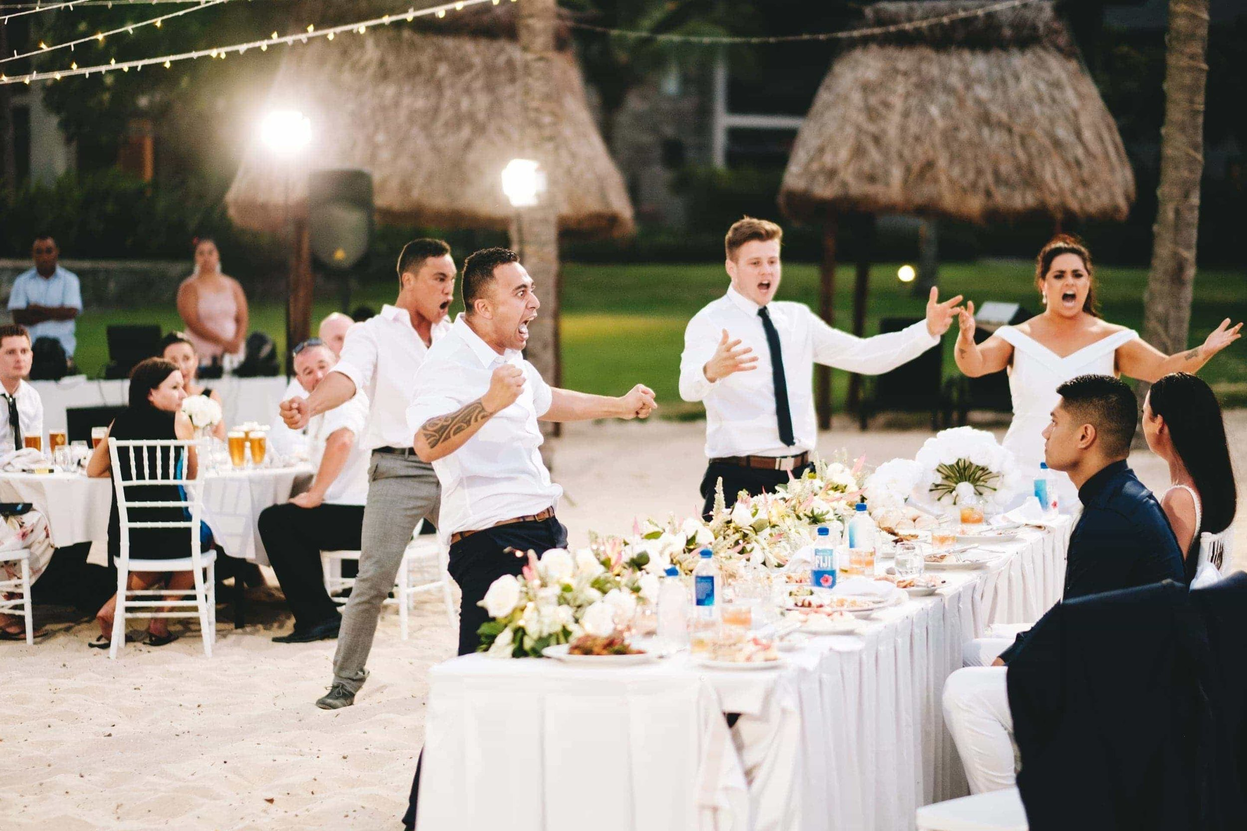 the groomsman and best man preform a traditional New Zealand Haka with guests for the wedding couple
