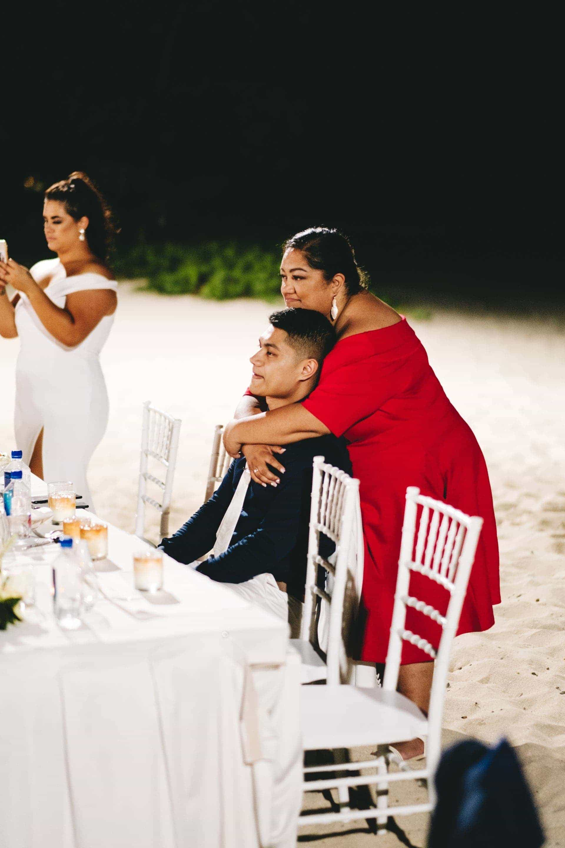 an emotional groom is hugged by his mother as they watch the bride and her father dance