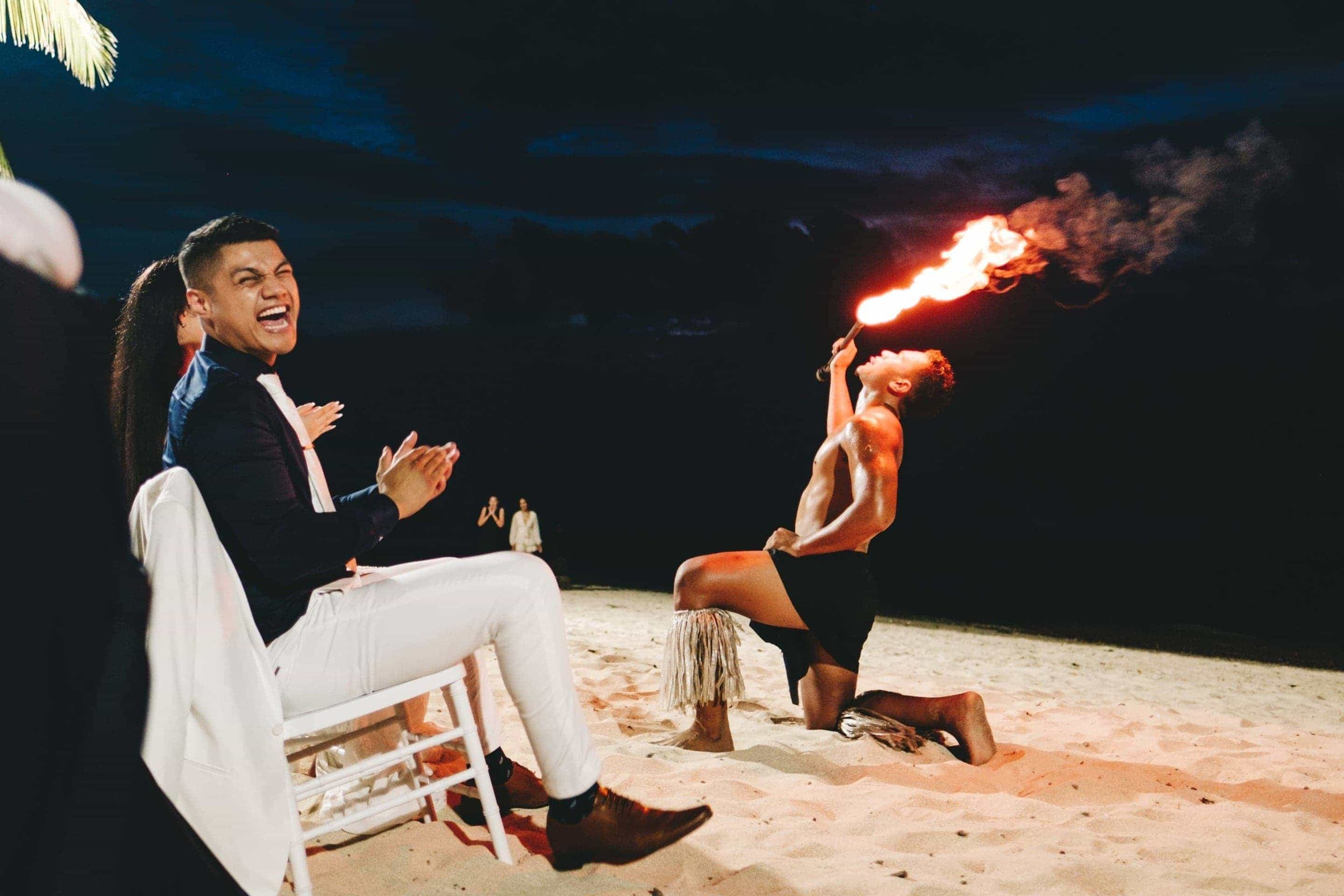 the groom laughing heartedly as a performer eats fire