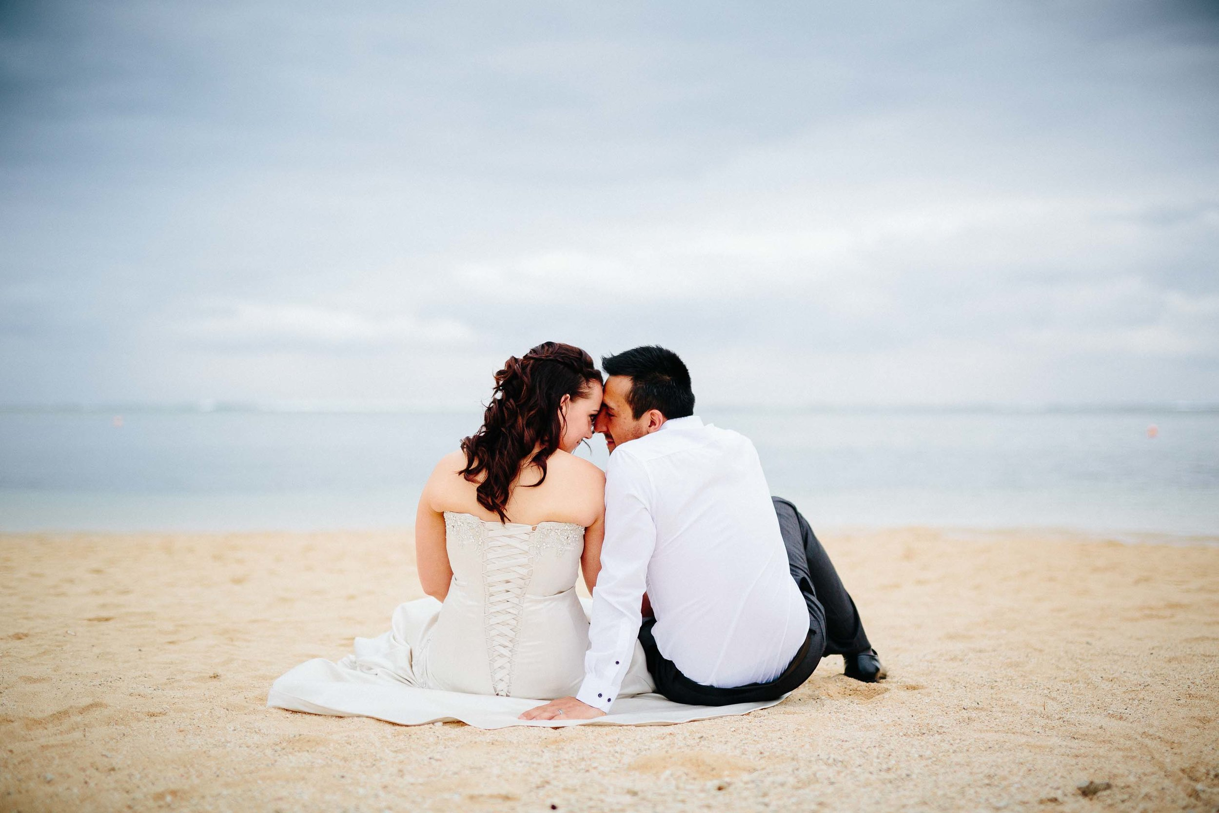 bride and groom sitting down on the beach kissing