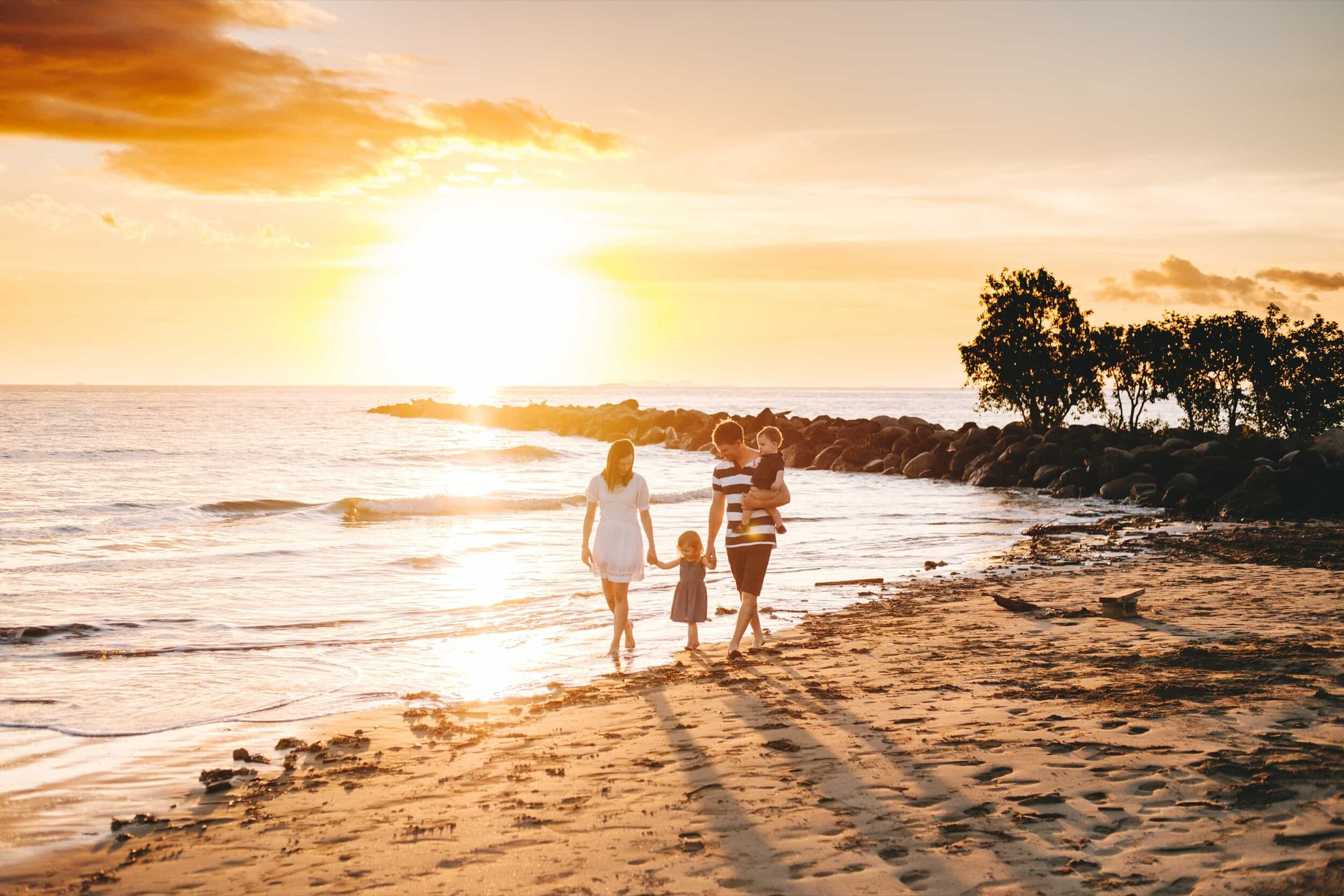 Family holiday photos along the Sheraton Fiji beach at sunset.