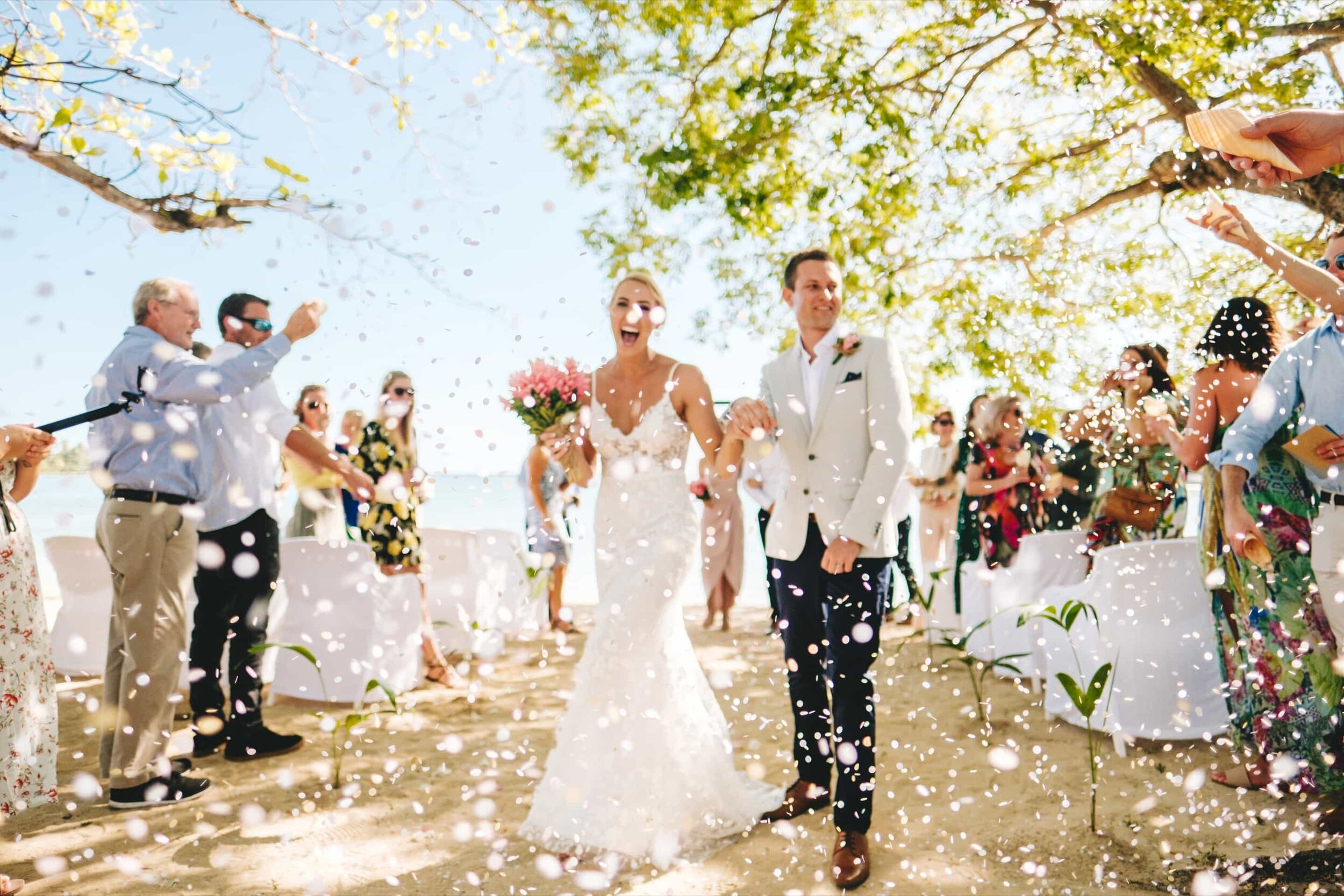 Out of focus photo of young married couple with an explosion of confetti surrounding them as they leave their wedding ceremony venoue on the beach at Musket Cove Resort Fiji