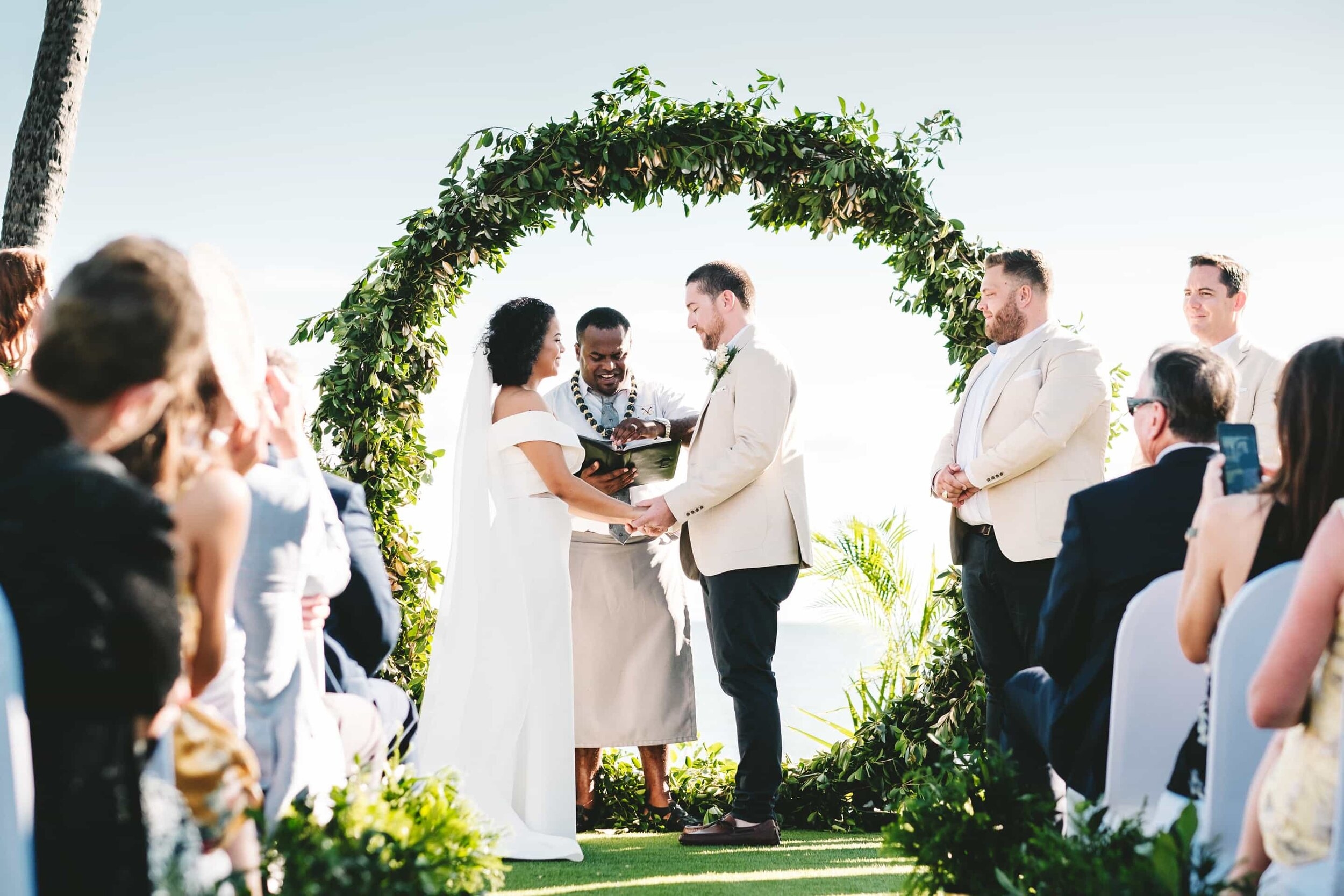 """Wedding ceremony at the Sheraton Fiji's """"the Wedding Lawn"""" with a lush circular green arch"""