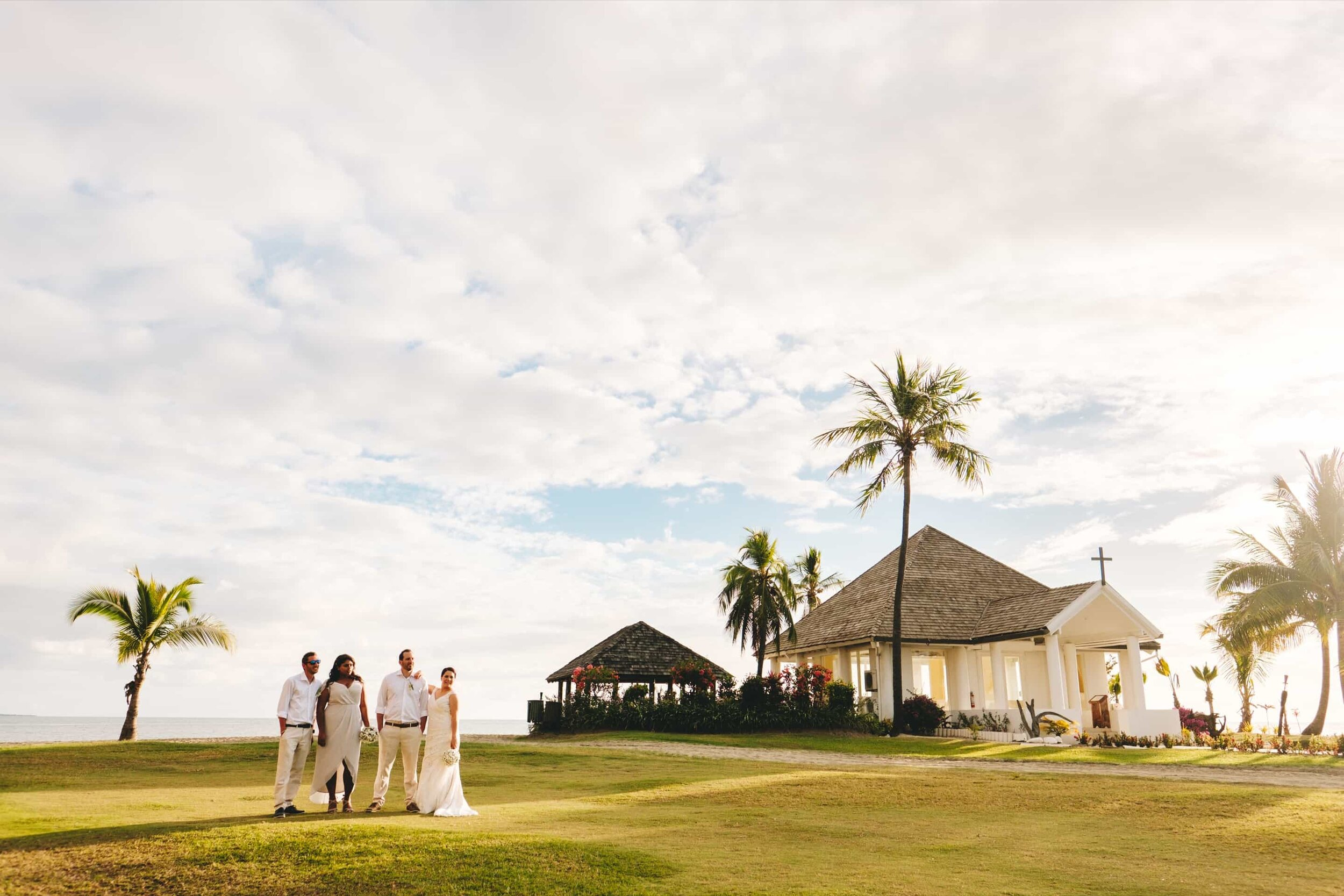 A bridal party posing in-front of the Sheraton Fiji's Wedding Chapel at Sunset