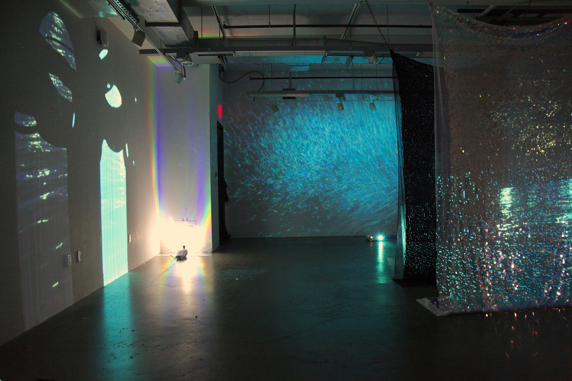 between body - 2018, Sequins, cracked mirror, paint, boxing gloves, flashlights, holographic vinyl, two identical videos of the Atlantic Ocean at night, one has been color manipulated to be a Caribbean Sea blue.