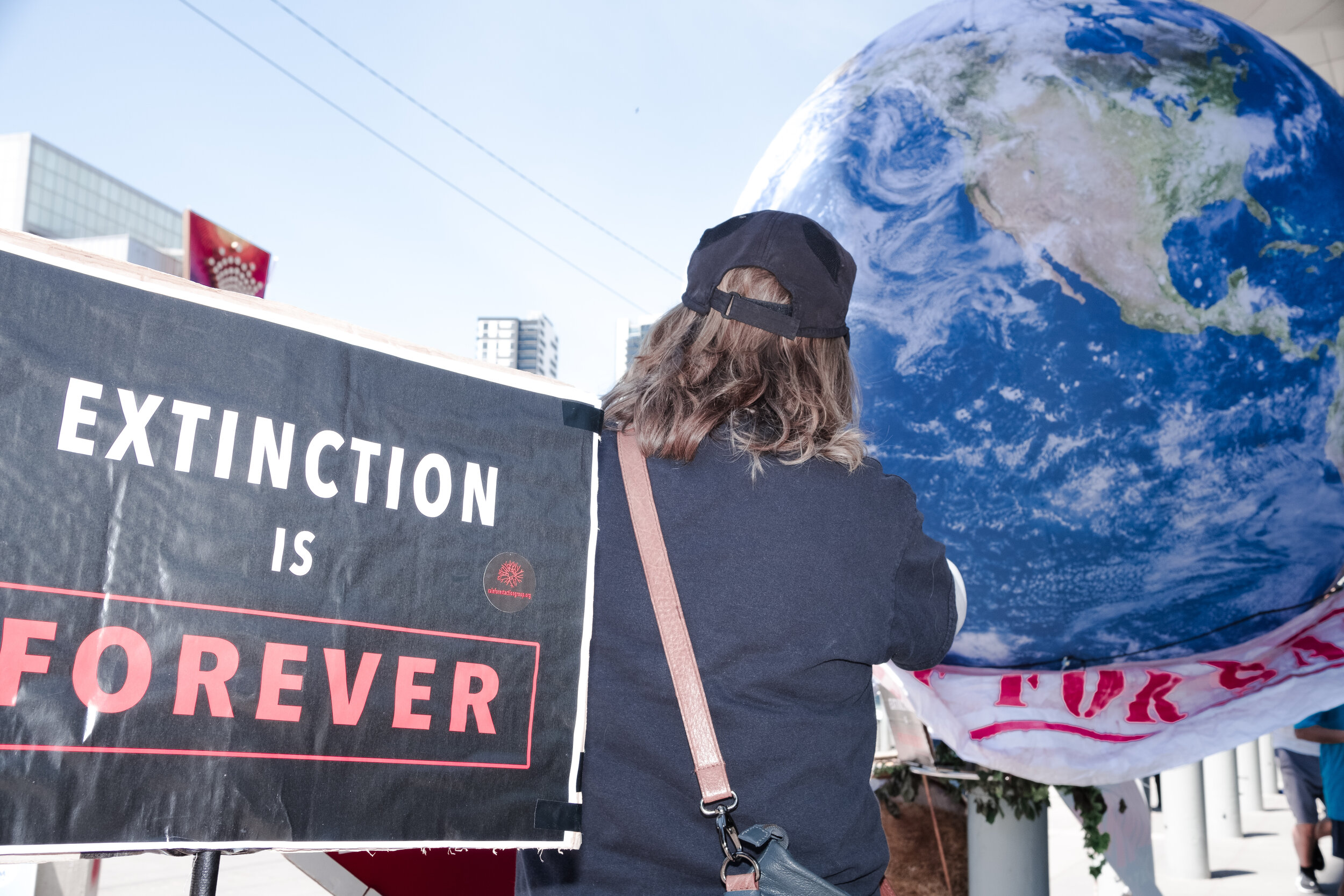 A woman stands in front of a giant inflatable Earth brought to the rally by protesters. (Photo: Jeremy Gan)