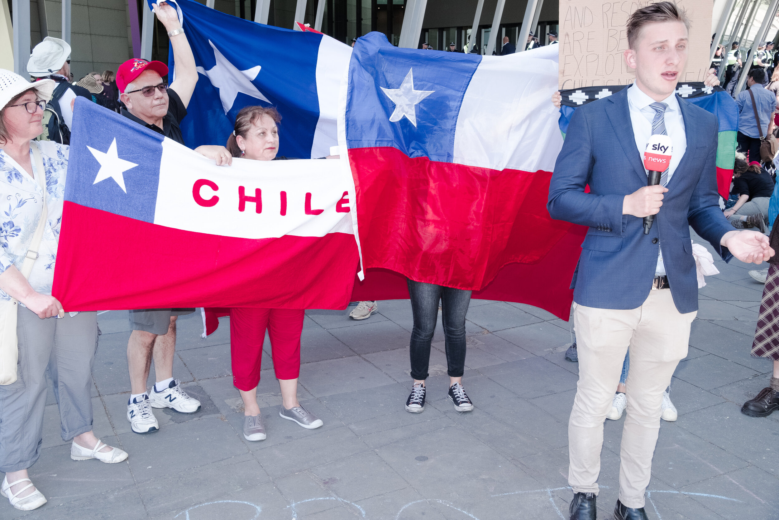 Protesters wave the Chilean flag behind a Sky News Reporter. The rally supported the recent mass protests in Chile that fought against corporations privatising lands. (Photo: Jeremy Gan)