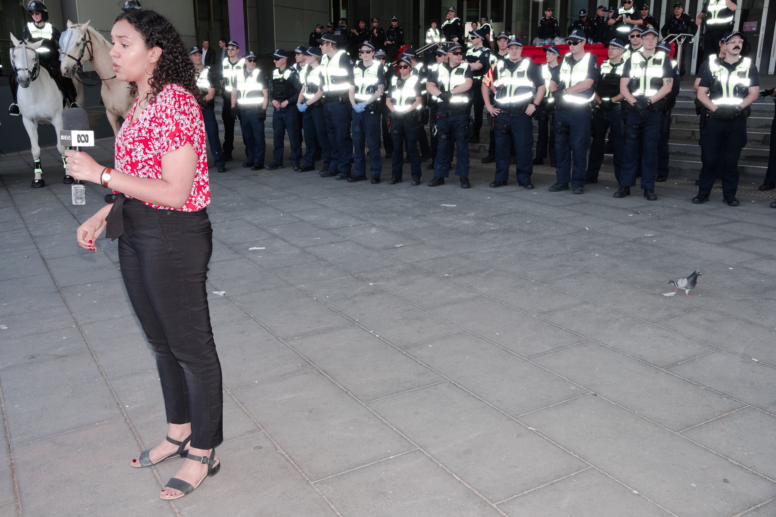 An ABC journalist reports in front of a line of police officers. (Photo: Jeremy Gan)