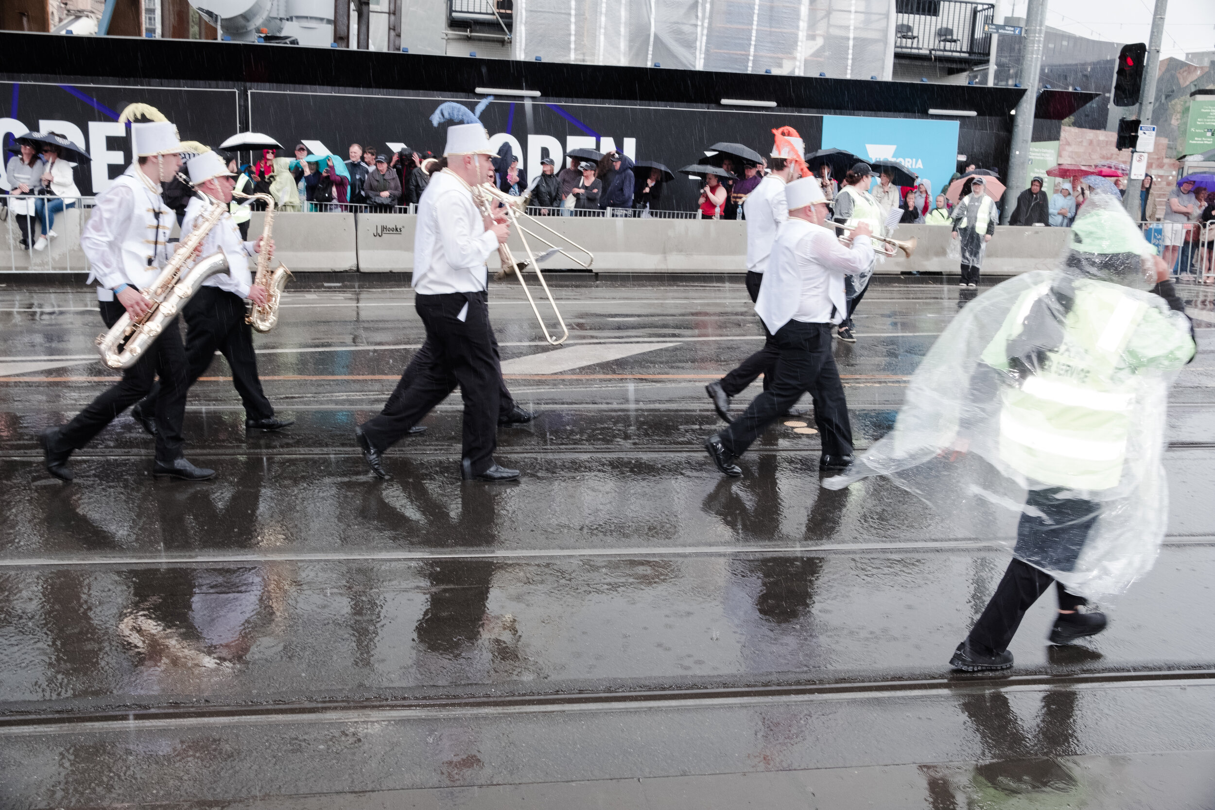 Performers and staff rush through the parade to escape heavy rain. (Photo: Jeremy Gan)