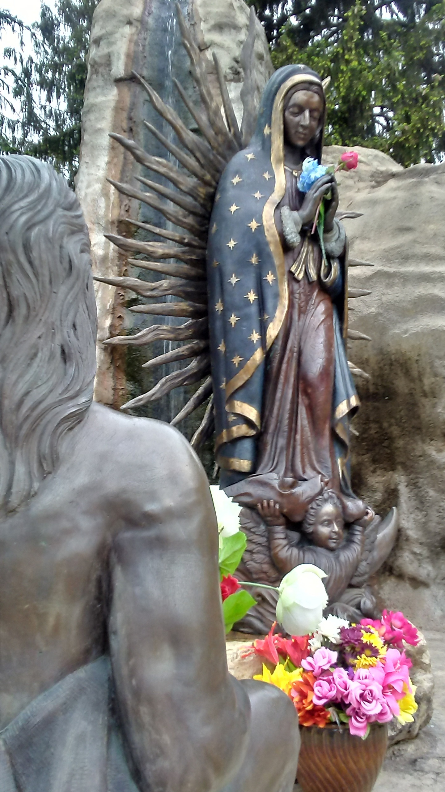 statue of St Juan Diego gazing upon Our Lady of Guadalupe
