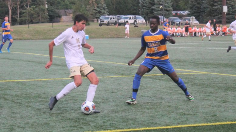 Noblesville's Owen Mejia (left) prepares to kick the ball as Carmel's Babacar Diatta plays defense during the Greyhounds-Millers boys soccer game Thursday at Carmel's Brian Murray Stadium. The game, which was the season opener for both teams, ended in a 1-1 tie. (Richie Hall)