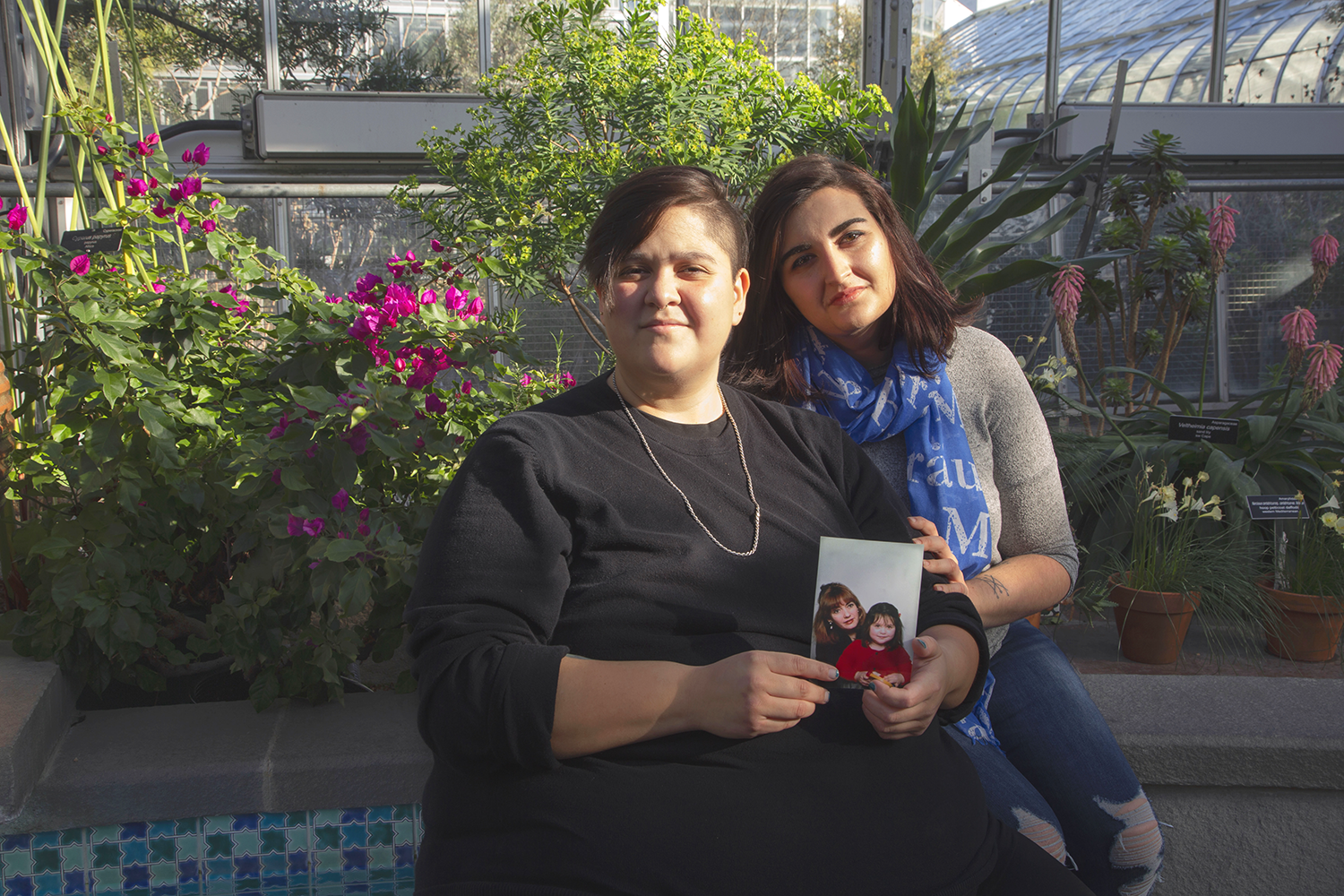 Nahuel Aránguiz poses with their friend Kat Greene and a picture of them and their mom at the United States Botanical Garden on January 28th, 2019.  Segunda Familia  is a 3-portrait project that demonstrates Queer people with their chosen family. As queer people, our families aren't always supportive of us, so we search for family figures in our communities.