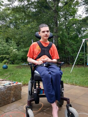 A young man in a wheelchair smiles from his patio.