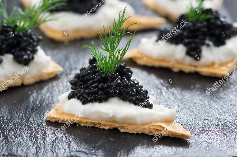 stock-photo-crackers-with-cream-cheese-and-black-caviar-horizontal-211444606.jpg